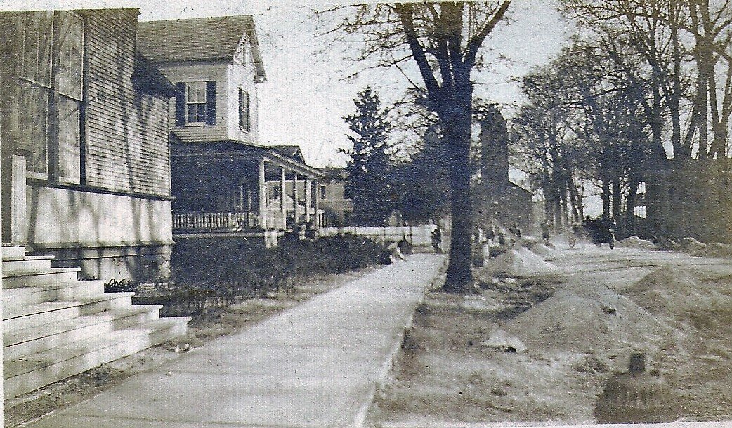 Looking south along Church Street about 1920 from the corner of Hampton Avenue, Temple Sinai is on the left and Trinity United Methodist Church is in the distance at the end of Church Street. Workers in the middle distance are preparing the street to be paved.