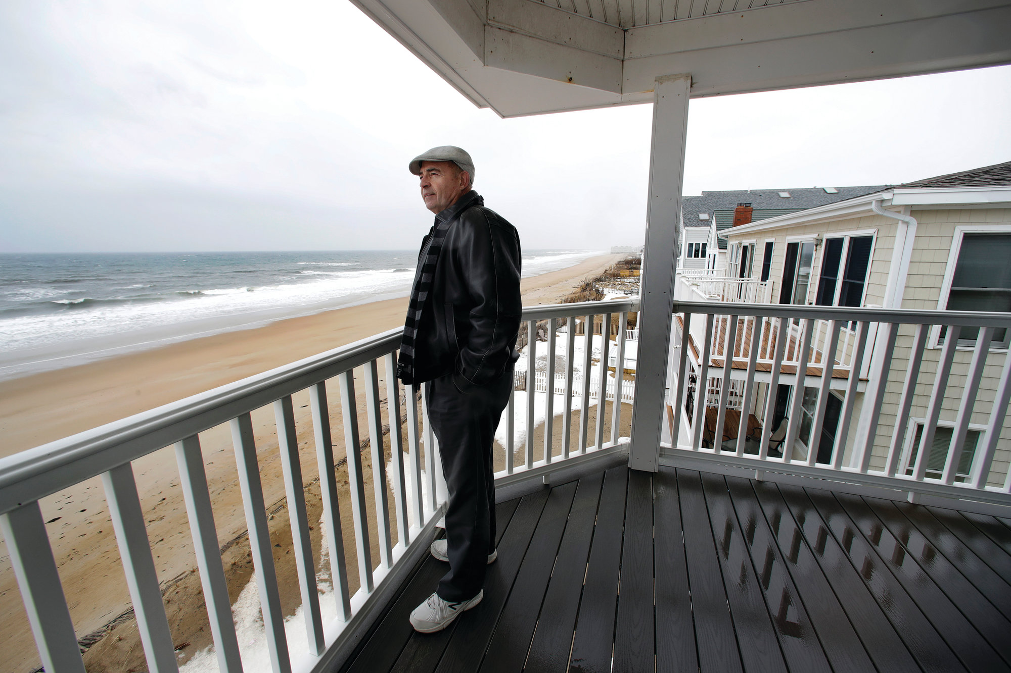 THE ASSOCIATED PRESS  Real estate agent Tom Saab stands on a oceanfront deck at a condo he developed in Salisbury, Massachusetts. Academic researchers say concerns over rising sea levels and increased flooding are having subtle but significant impacts on coastal property values.