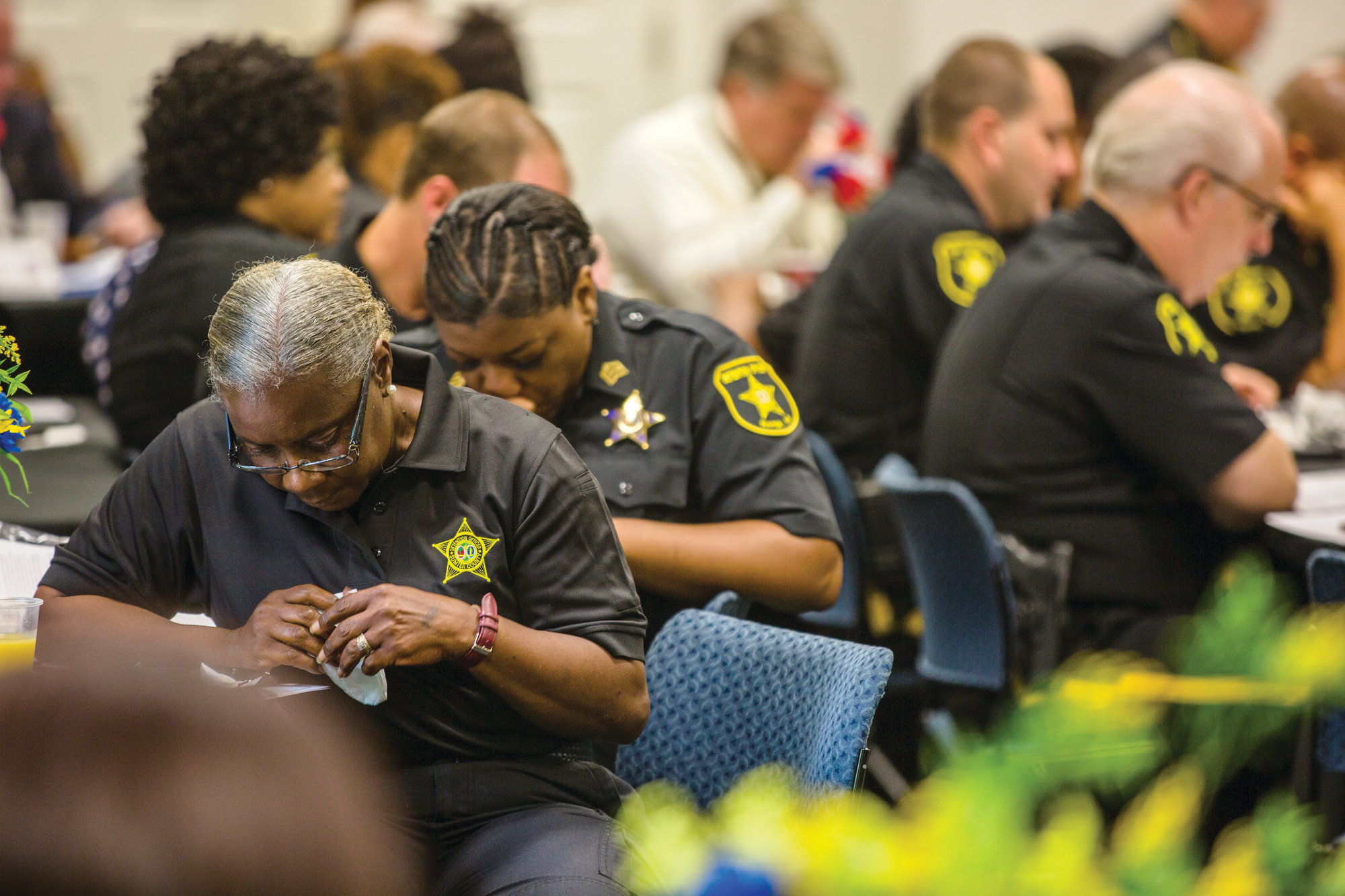 A detention officer with Sumter County bows her head along with others at the prayer breakfast on Tuesday.