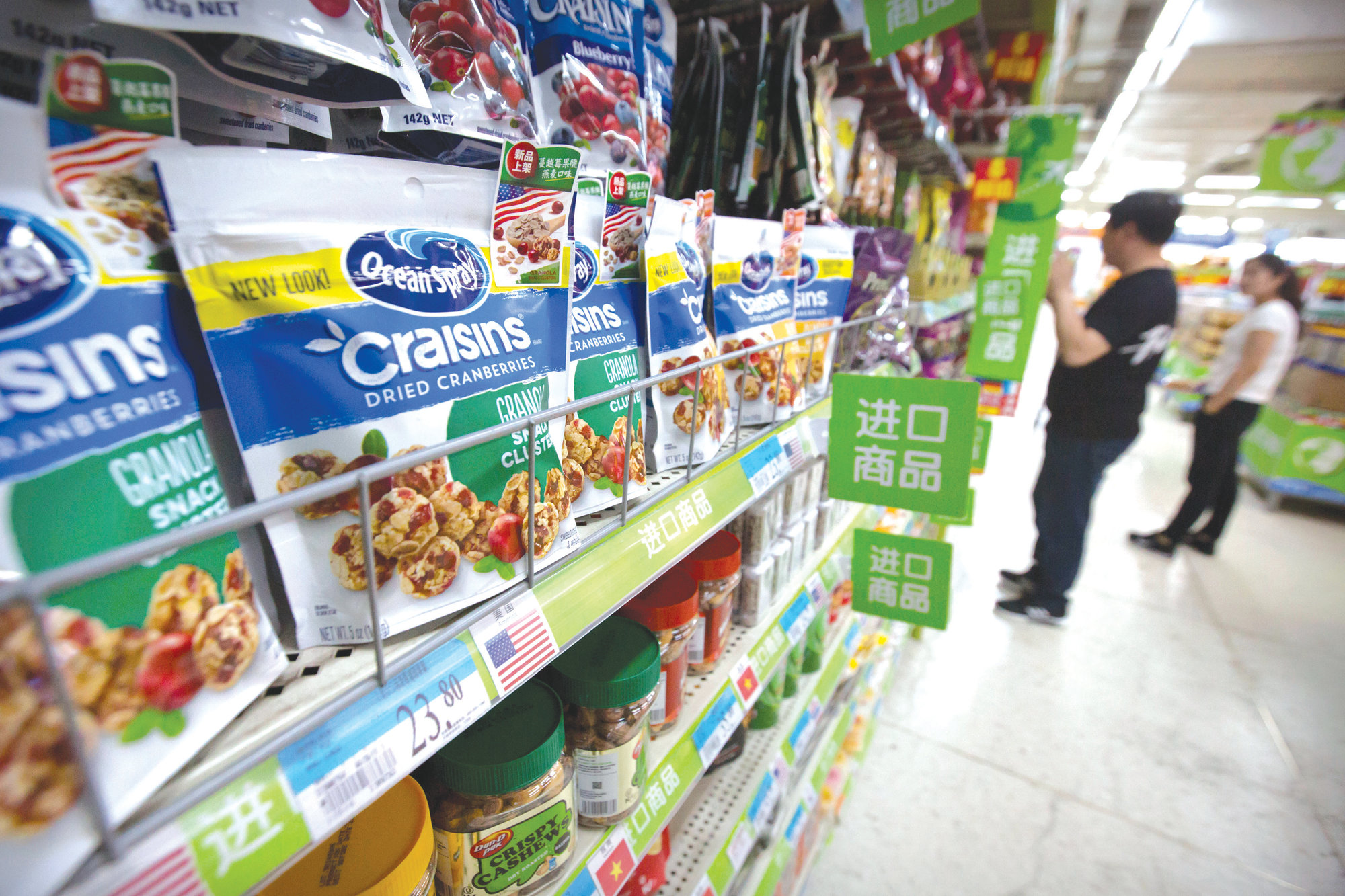 Customers shop near dried cranberry products from the United States at a supermarket in Beijing on Tuesday. Sending Wall Street into a slide, China announced higher tariffs Monday on $60 billion worth of American goods in retaliation for President Donald Trump's latest penalties on Chinese products.