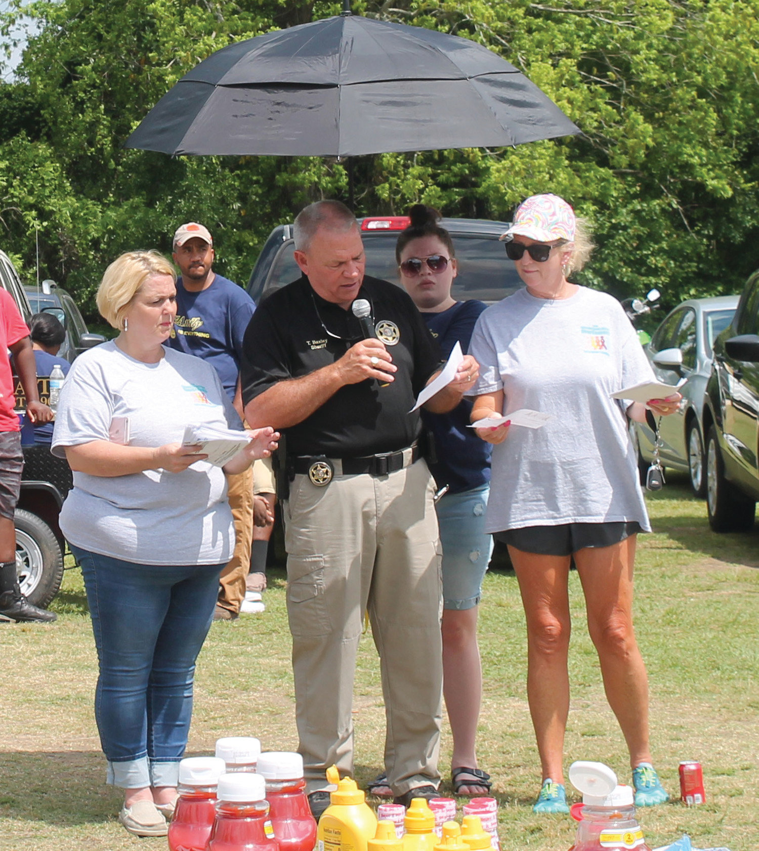 Clarendon County Sheriff Tim Baxley, center, read the names of the individuals listed on the dozens of luminaries that lined the fences at the 2019 Clarendon County Cancer OverComers' Walk.