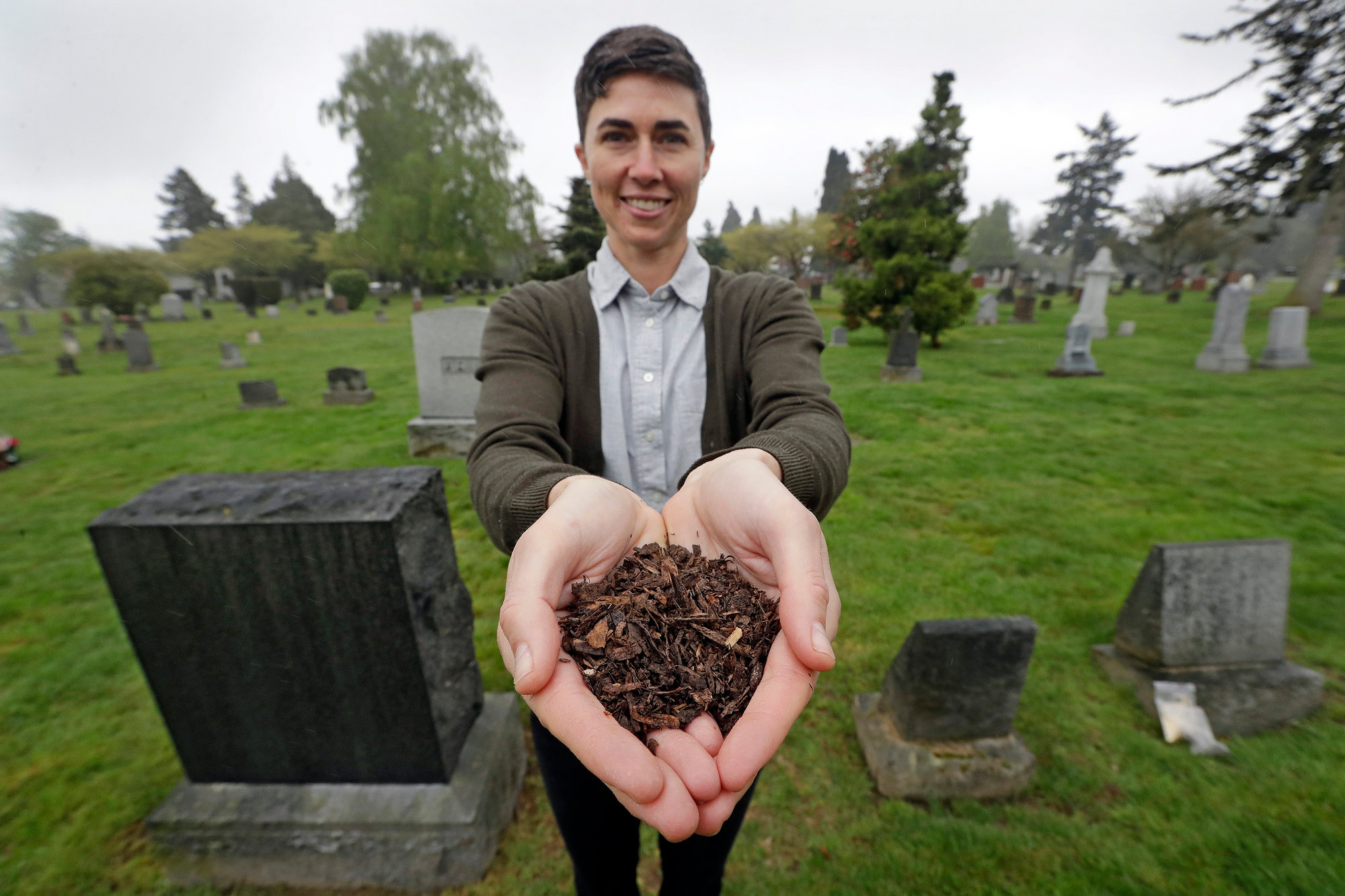 "Katrina Spade, the founder and CEO of Recompose, displays a sample of the compost material left from the decomposition of a cow, using a combination of wood chips, alfalfa and straw, as she poses in a cemetery in Seattle. Washington is set to become the first state to allow the burial alternative known as ""natural organic reduction"" that turns a body into soil in a matter of weeks."