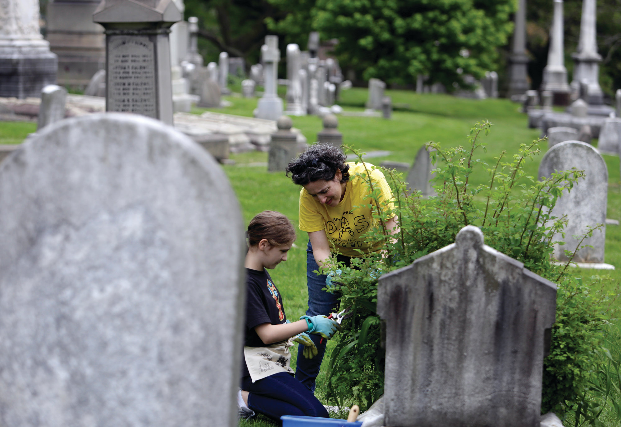 PHOTOS BY THE ASSOCIATED PRESS  Celina Gray, right, and her daughter Kalliope Kourelis, trim a rose bush growing on the cradle grave of Mary Glenn recently at the Woodlands Cemetery in Philadelphia.