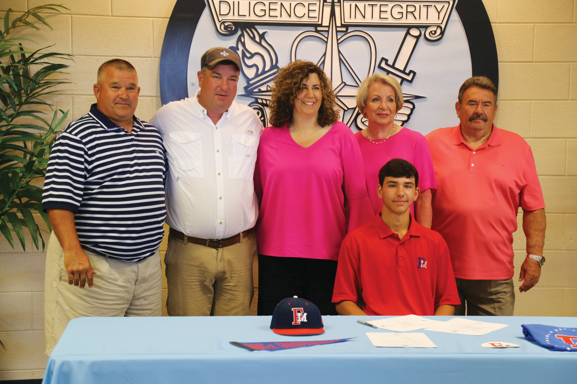 Surrounded by family and his coach, Wilson Hall's Tanner Epps signed on to play baseball at Francis Marion University during a signing ceremony at the school on Tuesday.