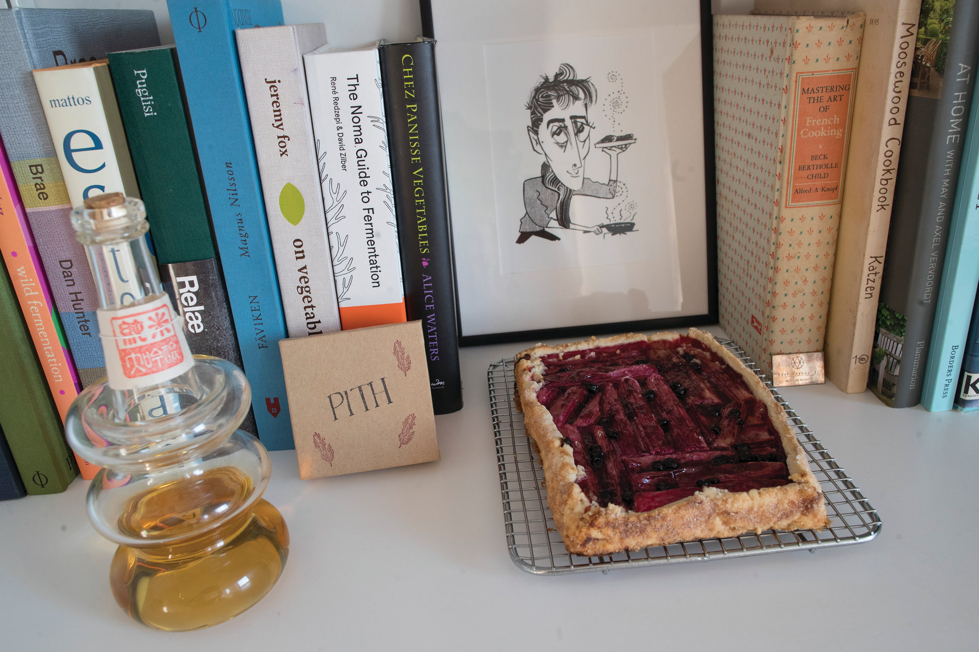 THE ASSOCIATED PRESS  A rhubarb tart is displayed with a caricature of Jonah Reider and his cookbooks in his New York apartment. In the competitive food world, Reider is a millennial whose cooking is opening doors to adventures far beyond food.