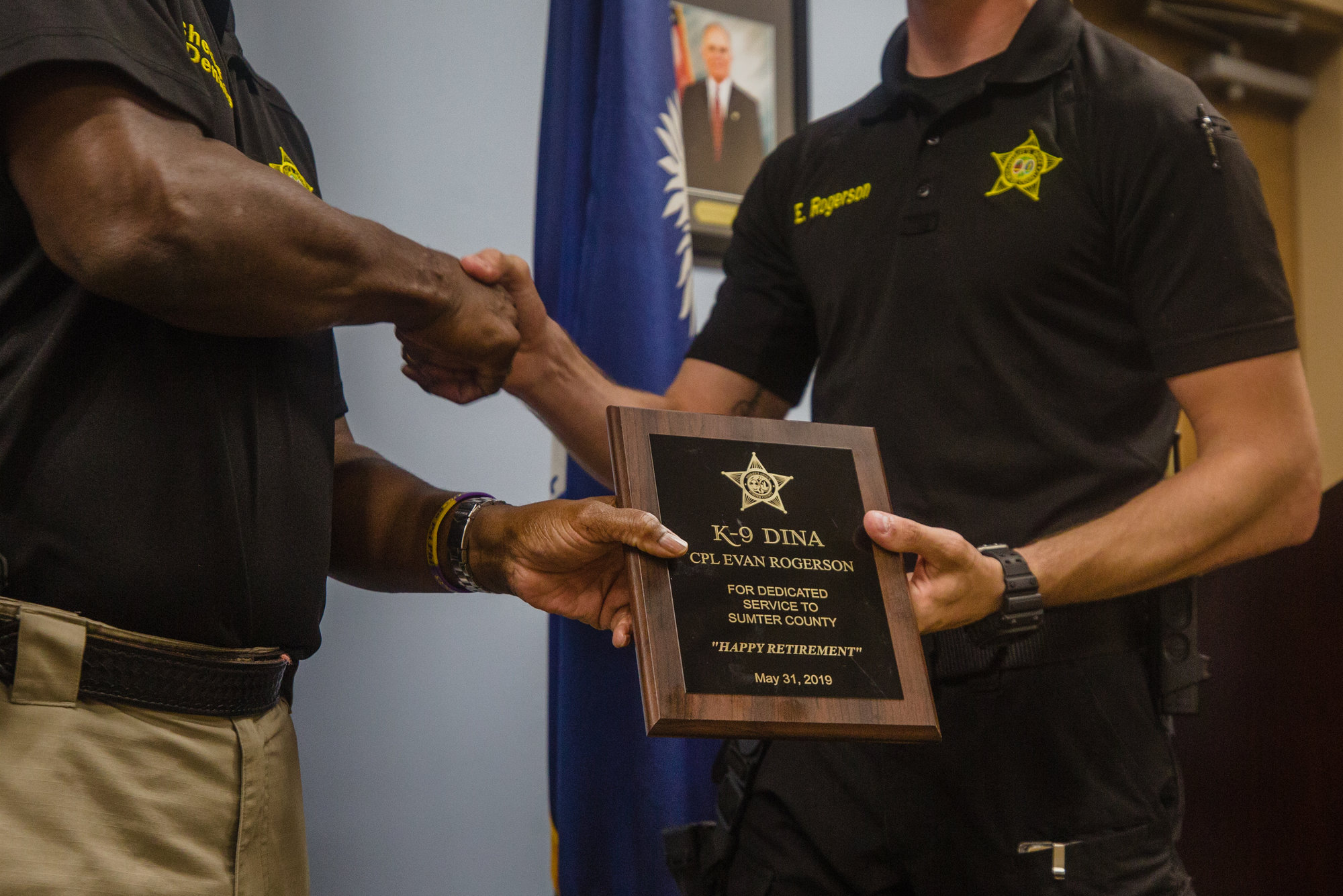 Sumter County Sheriff Anthony Dennis awards Cpl. Evan Rogerson a plaque congratulating K-9 Dina on her retirement.