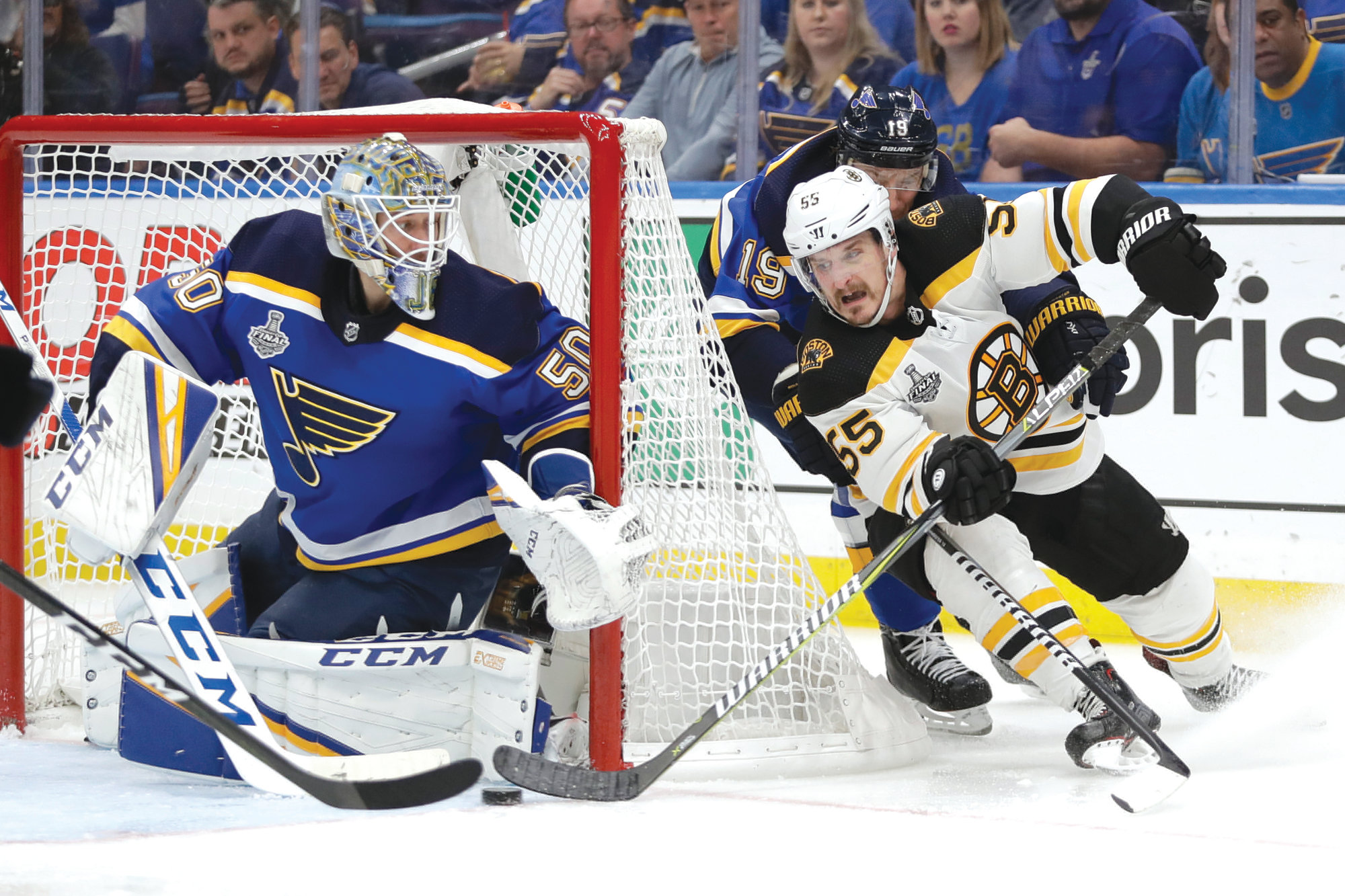 Boston Bruins center Noel Acciari (55) rounds the net against St. Louis Blues goaltender Jordan Binnington (50) during Game 6 of the NHL hockey Stanley Cup Final on Sunday in St. Louis. The Bruins won 5-1 to even the series 3-3.