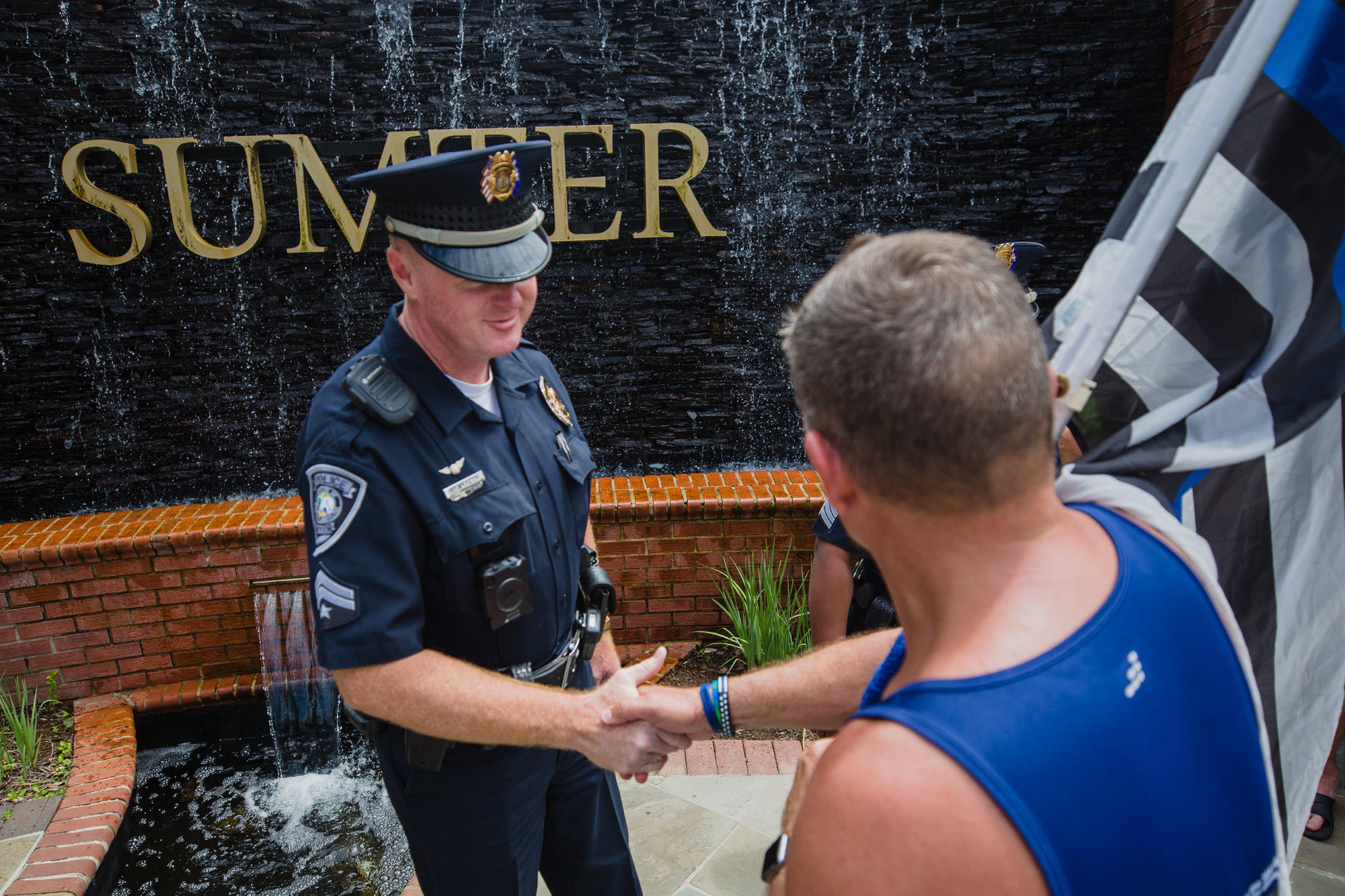 Daniel Watson shakes hands with Officer Brian Kyzer with the Sumter Police Department after completing his part of the run.