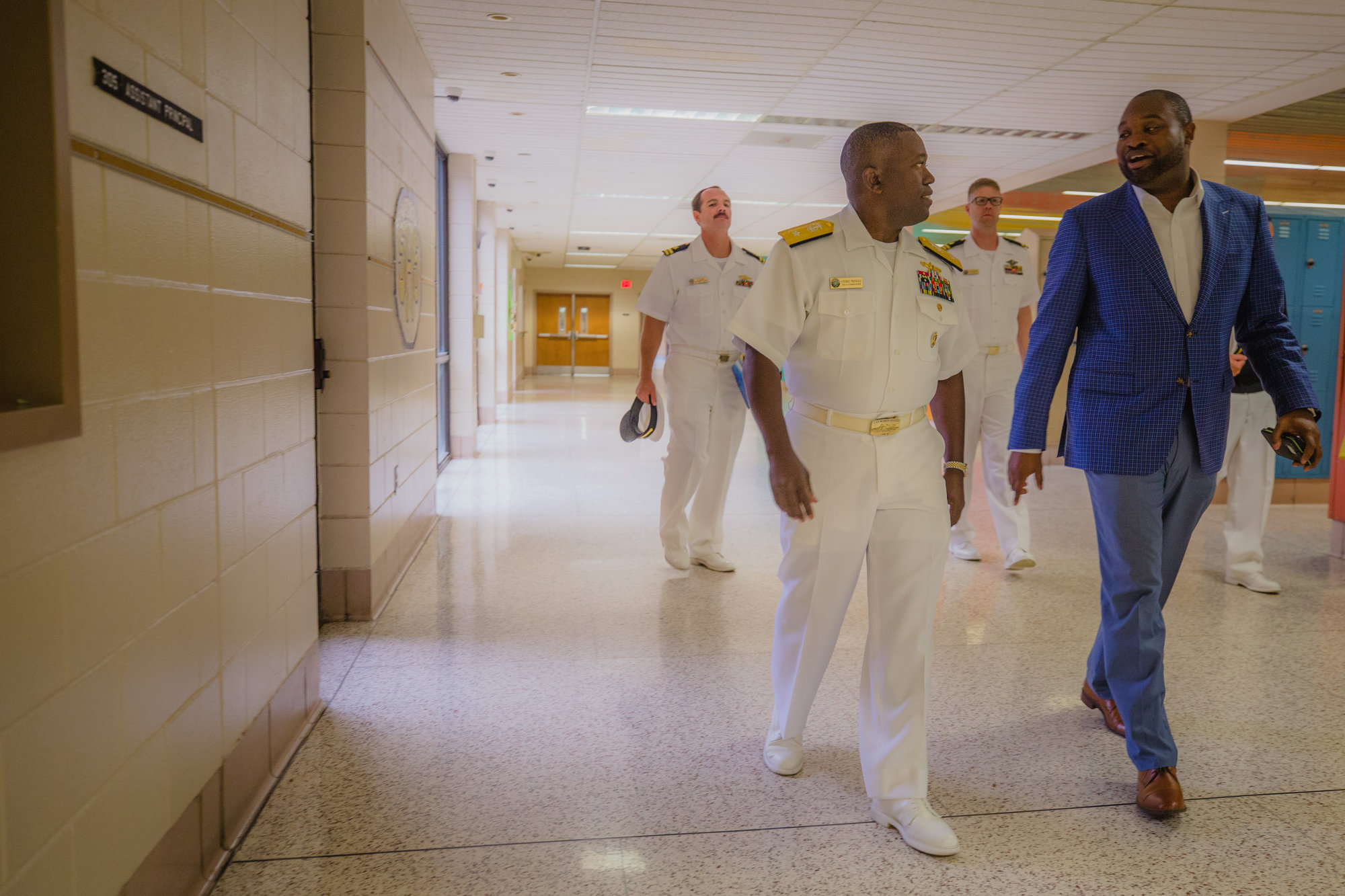 Rear Adm. Cedric Pringle walks through the halls of Sumter High School with Principal Nicholas Pearson on Monday during his visit to Sumter.