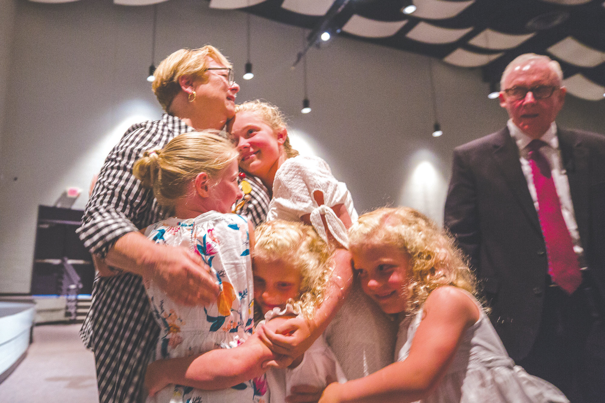 Debbie Hamm hugs her grandchildren after her family surprised her at the end of the day during the E3 conference.