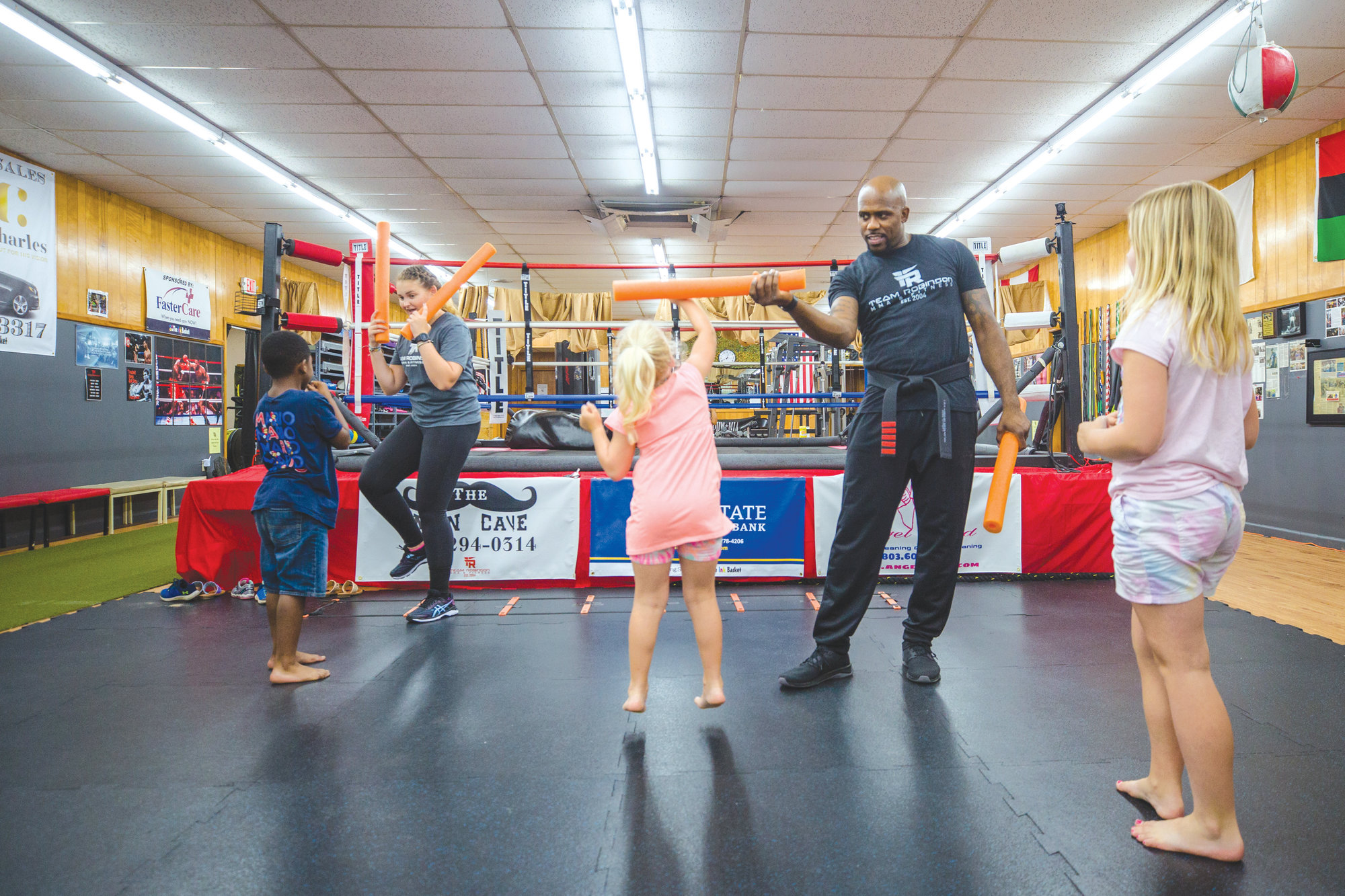 Jerome Robinson of Team Robinson MMA works with a student from Clubhouse Learning Center on Monday morning. The group makes a trip to the gym every Monday during the summer, where Jerome and his team teach them basic self defense skills and work outs.