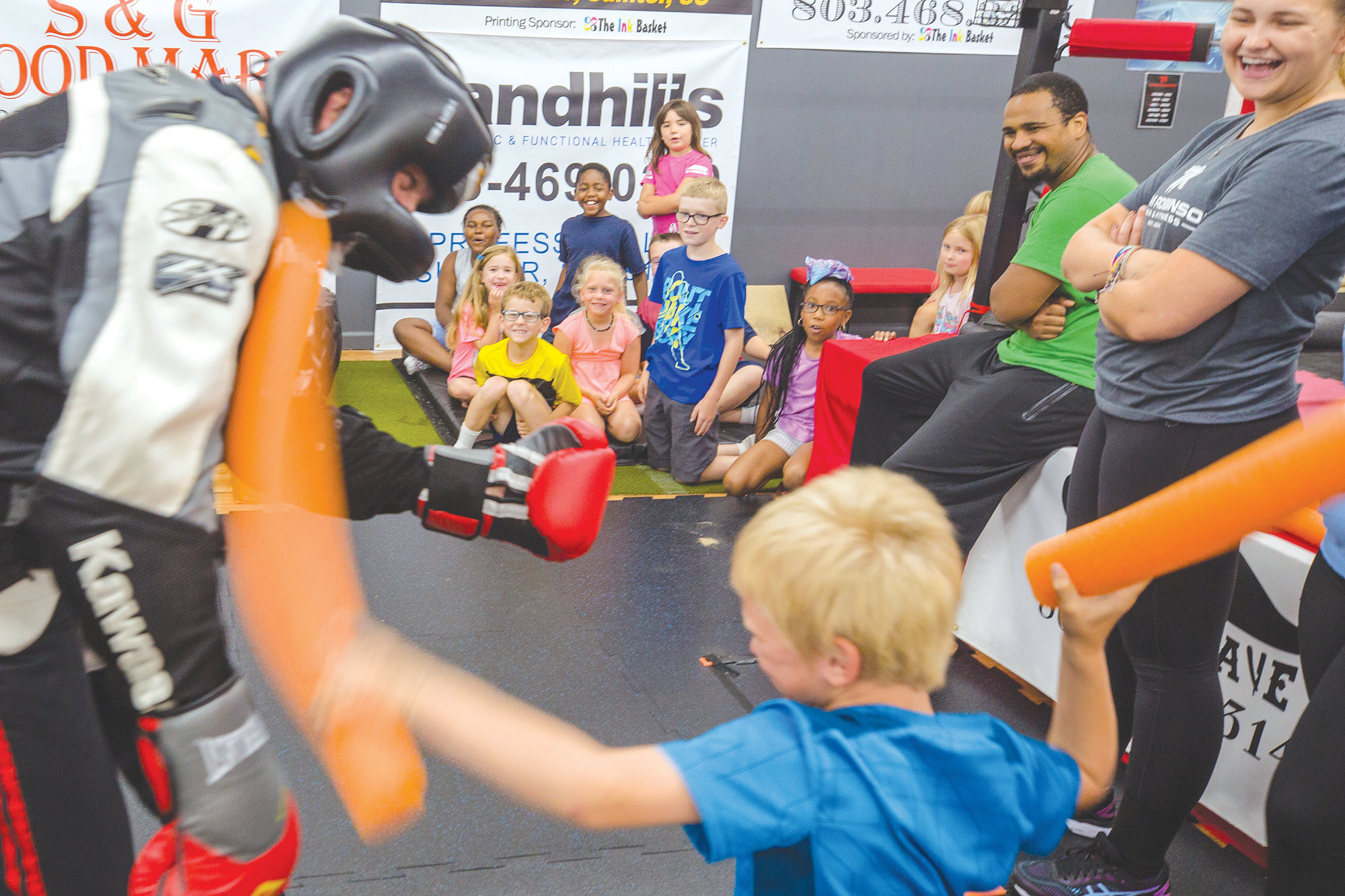 Students from Clubhouse Learning Center cheer on a classmate on Monday morning during their session at Team Robinson MMA in Sumter. The group makes a trip to the gym every Monday during the summer, where Jerome and his team teach them basic self defense skills and work outs.