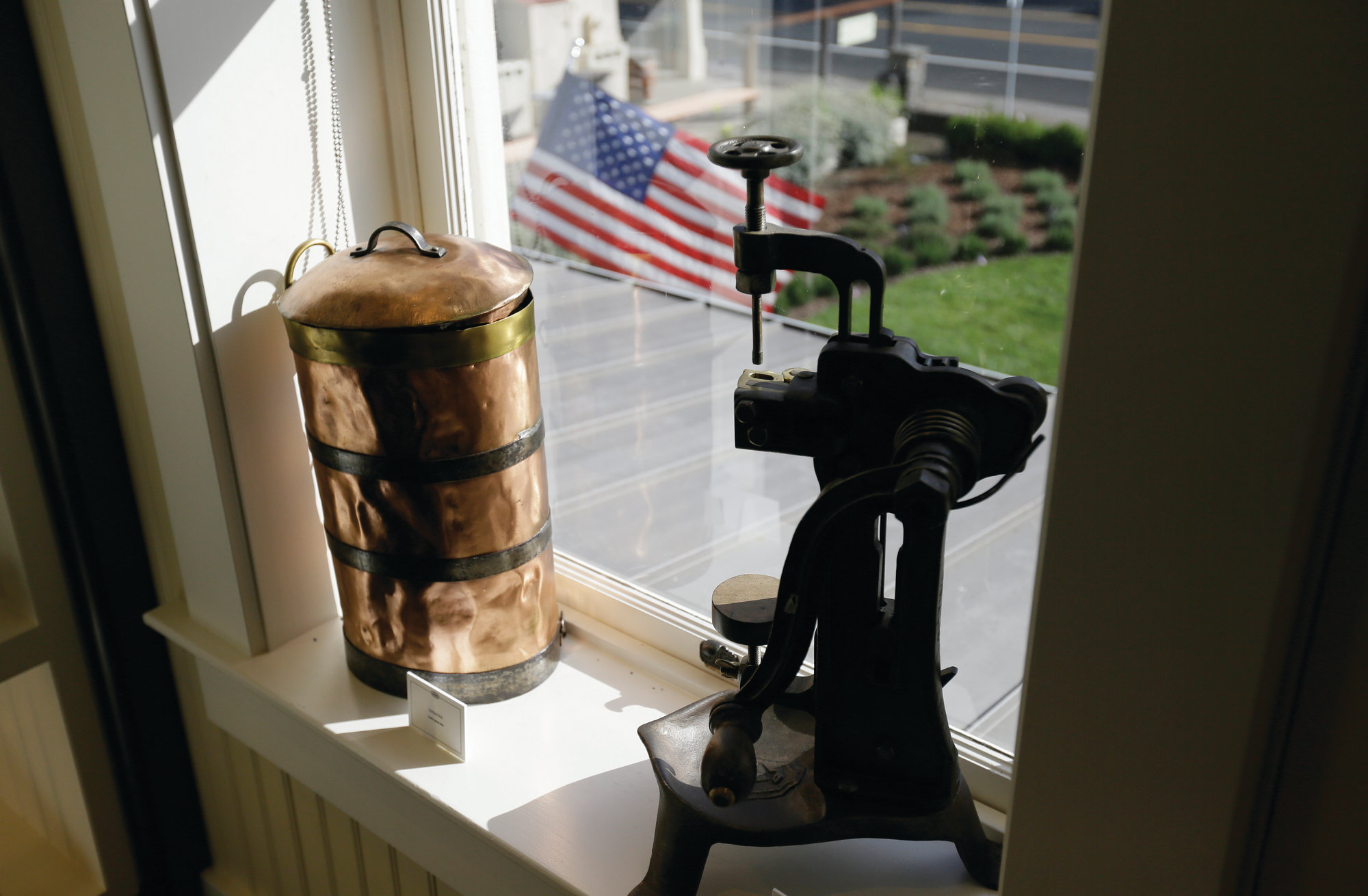 An old bottle corker and sprayer are seen in a window at the museum.