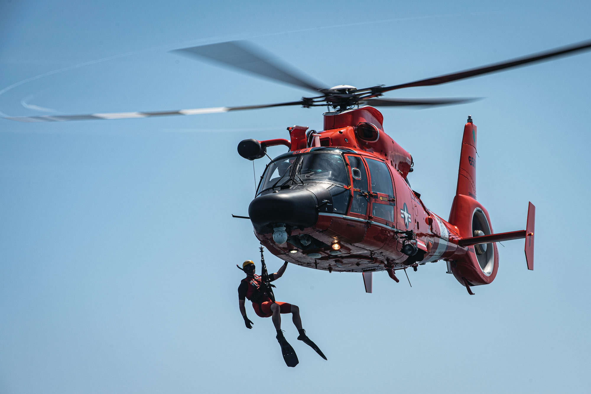 A U.S. Coast Guard rescue swimmer hangs off the side of an MH-65 Dolphin during the exercise.