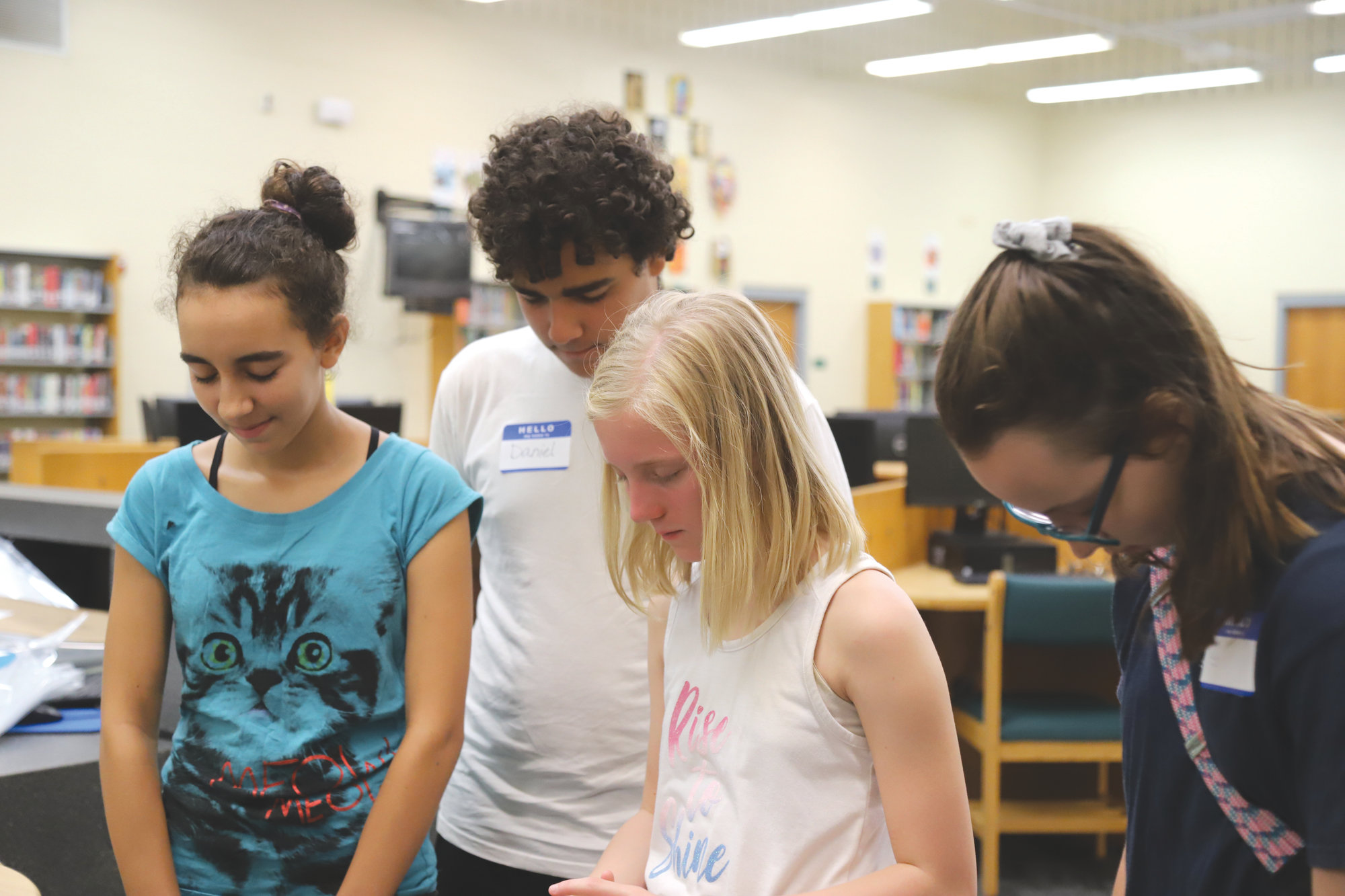 From left, Maria Fleitas, Daniel Fleitas, Dustie Estes and Lindsey Laity pray in the Chestnut Oaks Middle School library.