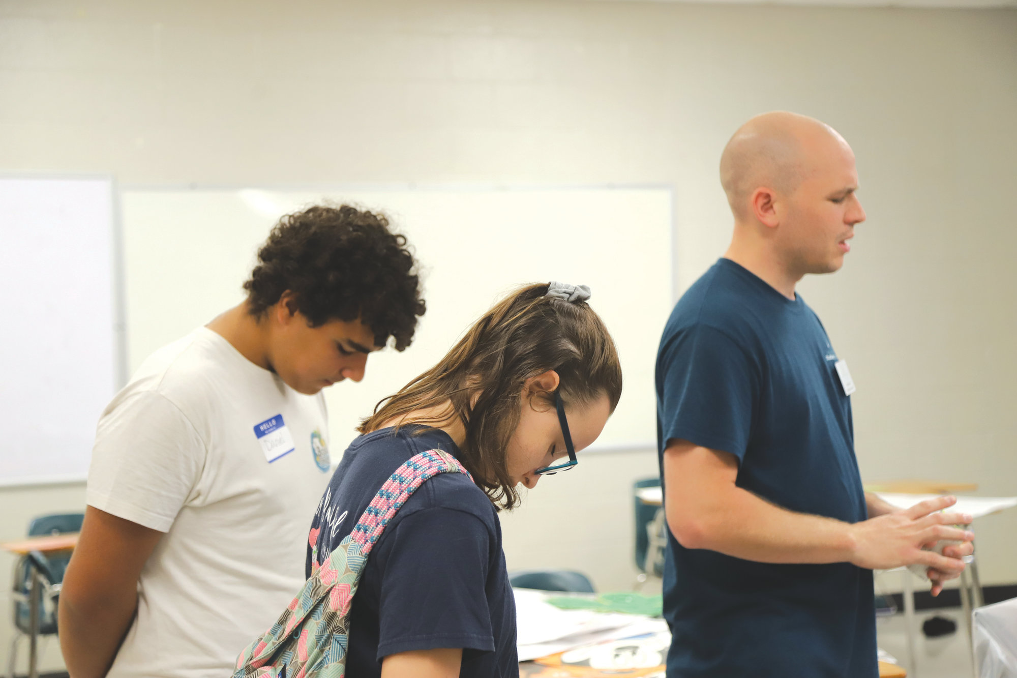 From left, Daniel Fleitas, Lindsey Laity and Matt Sprinkle say a prayer in a teacher's classroom at Chestnut Oaks Middle School.