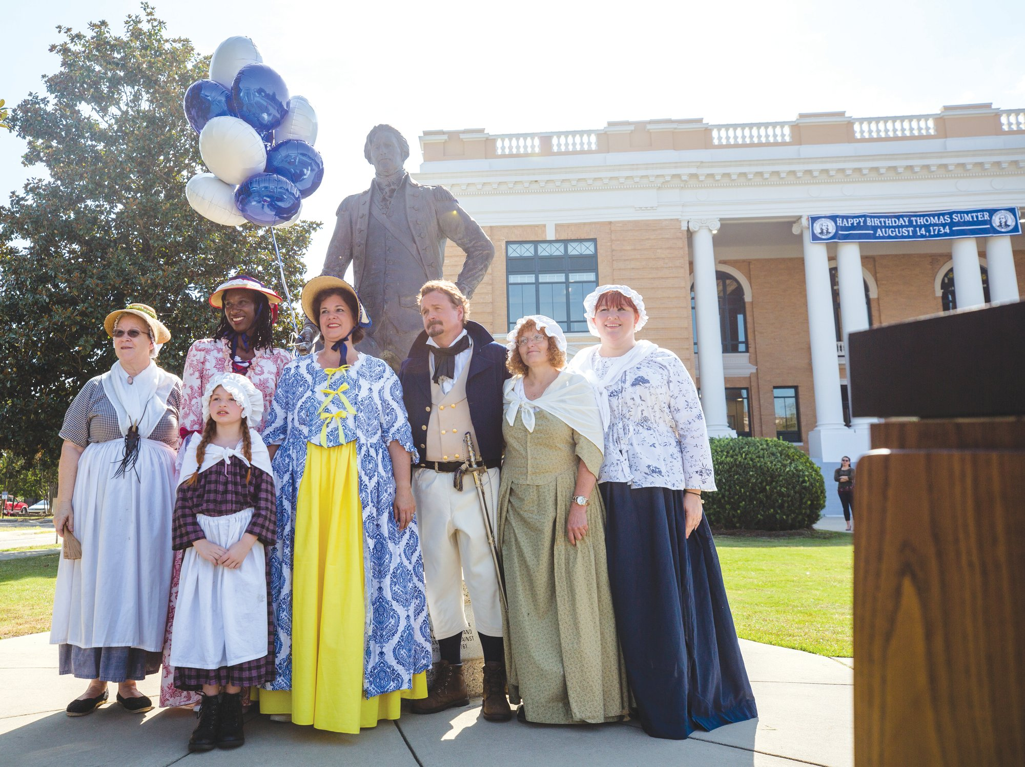A group in period clothing stands with the statue of Thomas Sumter on Wednesday.