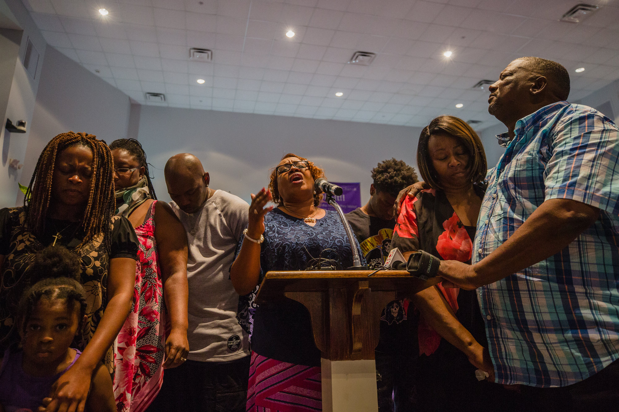 Minister Cleo Jackson prays with members of Nevaeh Adams' and Sharee Bradley's family during a prayer vigil at Trinity Missionary Baptist Church on Wednesday.