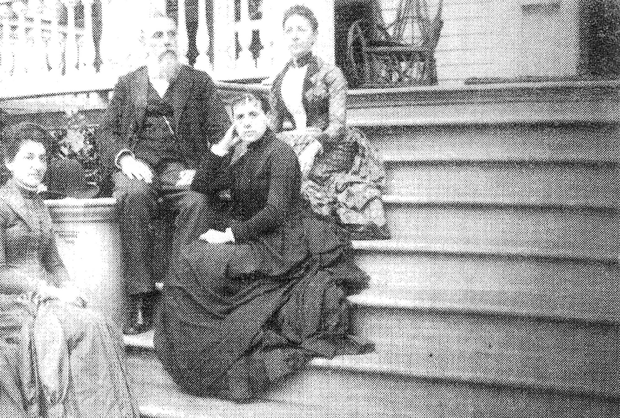A. A. Solomon is seen with his three daughters on the steps of their home.