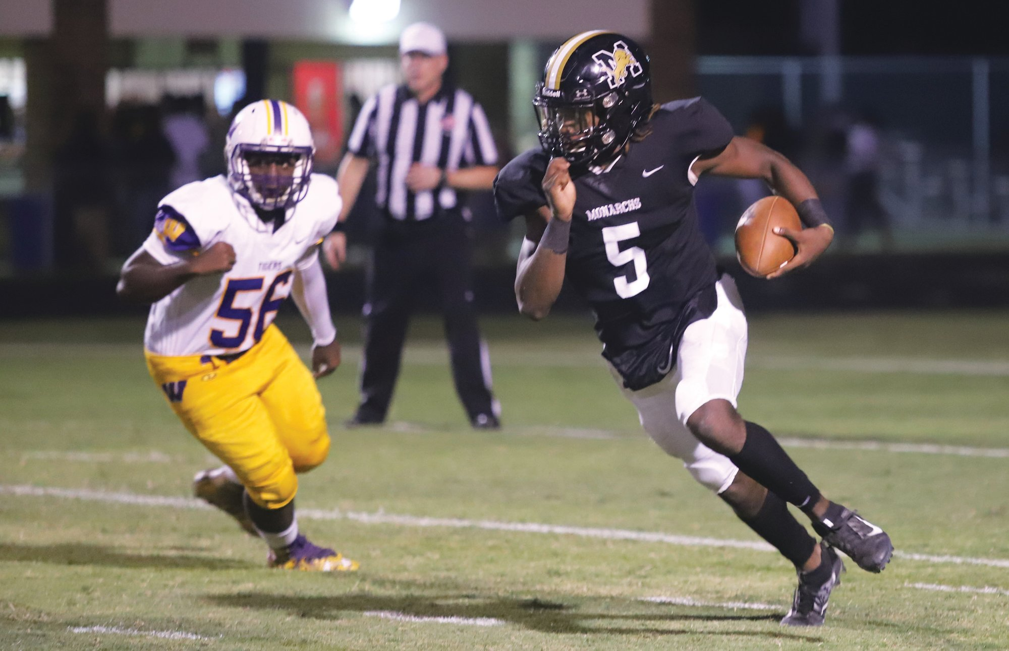 Manning quarterback Corey Graham (5) evades a Wilson defender in the first half of Manning's 35-13 loss to Wilson.