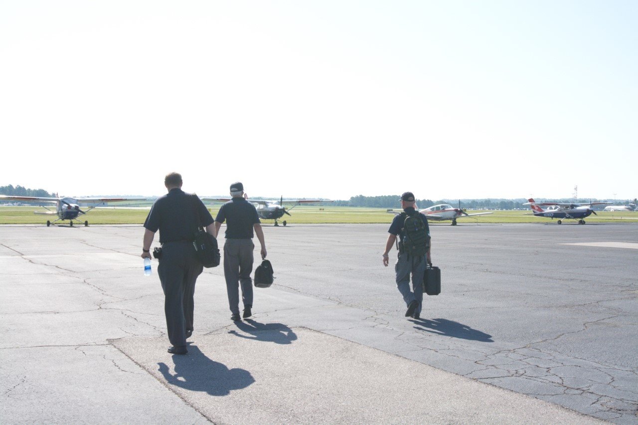 Three pilots from the Low Country Composite Squadron on Hilton Head Island head to the plane at Columbia Executive Airport to launch for their photography mission.