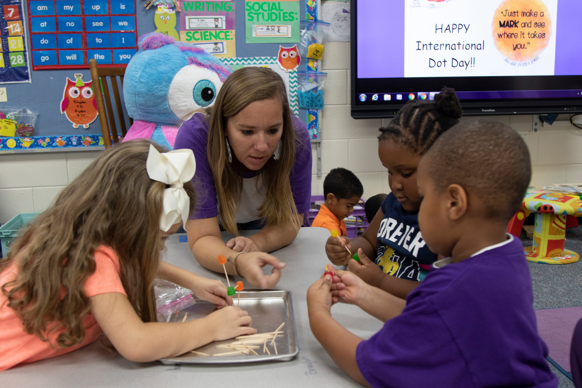 Stephanie McCormick helps her kindergarten students create something of their own using Dots candy and toothpicks.