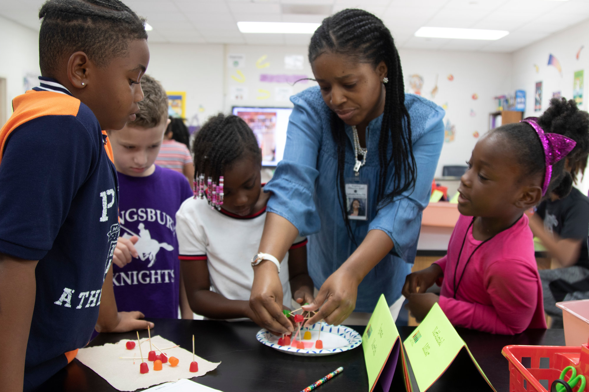 Lakesha Meredith helps her students create a house for the Three Little Pigs with students.
