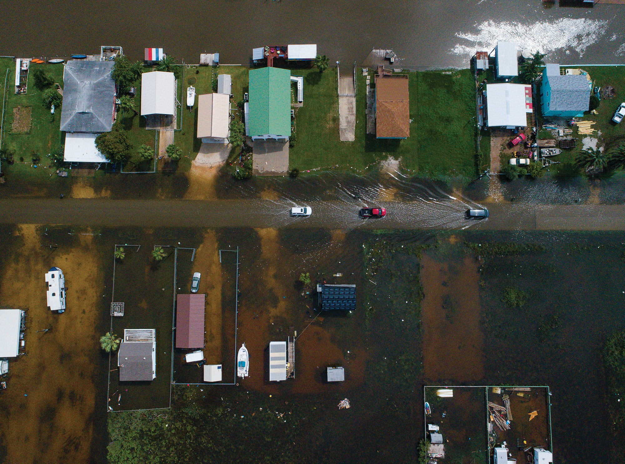 Mark Mulligan/Houston Chronicle via APCars drive on a flooded street in Sargent, Texas, as seen in this aerial photo Wednesday. Sargent received 22 inches of rain since tropical storm Imelda hit the area on Tuesday, according to Matagorda County Constable Bill Orton.