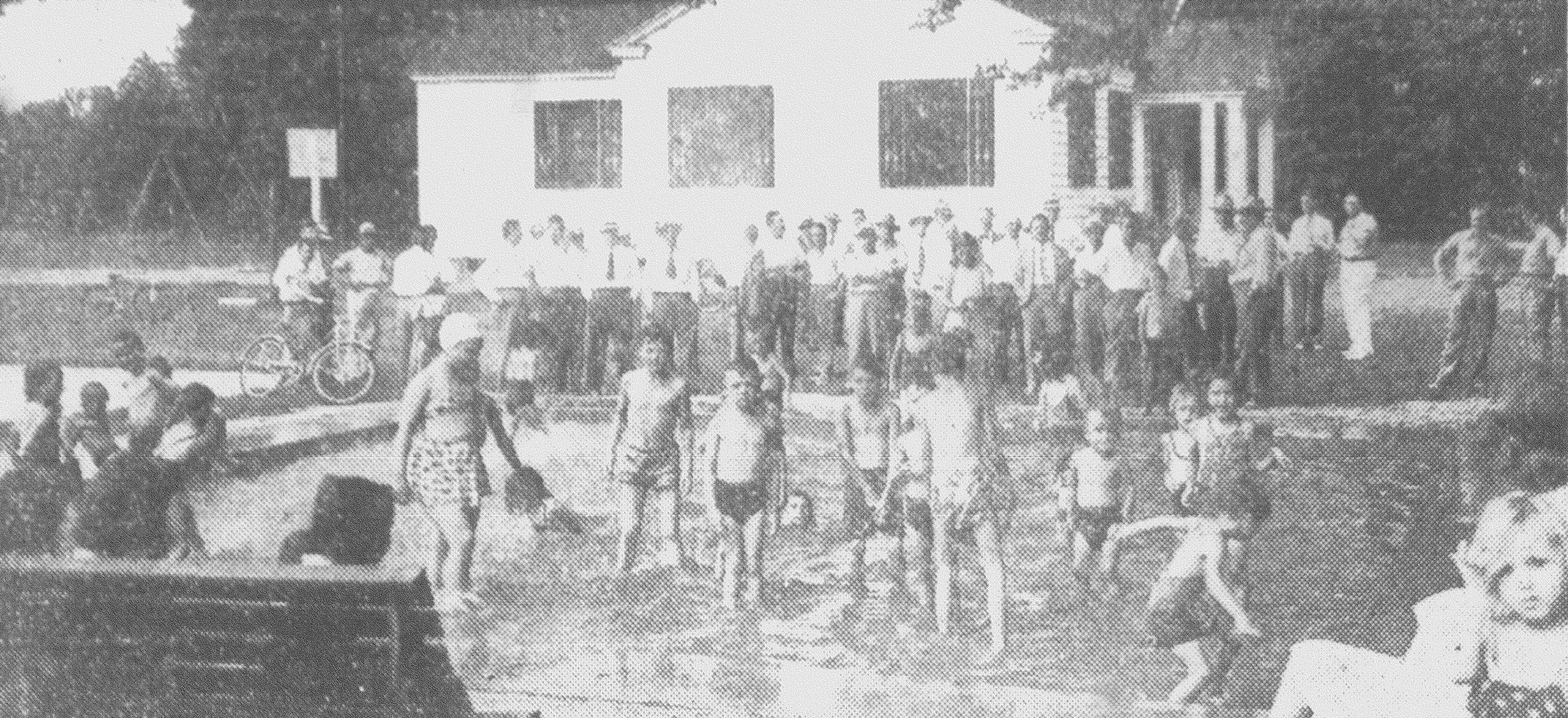 About 70 members of the Lions Club look on as children of the Jenkins Center playground splash in the new wading pool contributed by the club in July 1947. With the members are Mayor Edwin Boyle and members of the city council.