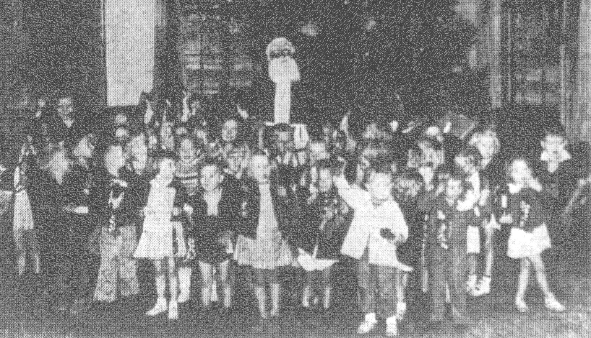 Santa Claus poses with 35 children who attended the Christmas party at Jenkins community center in December 1941. Each child received a present and a candy stocking at the party. A local organization sponsored the program of activity, at which an average of 30 children a day participated. When the picture above was taken, the children had just told Santa what they wanted for Christmas. They also played games at the party and sang a Christmas song and a patriotic song.