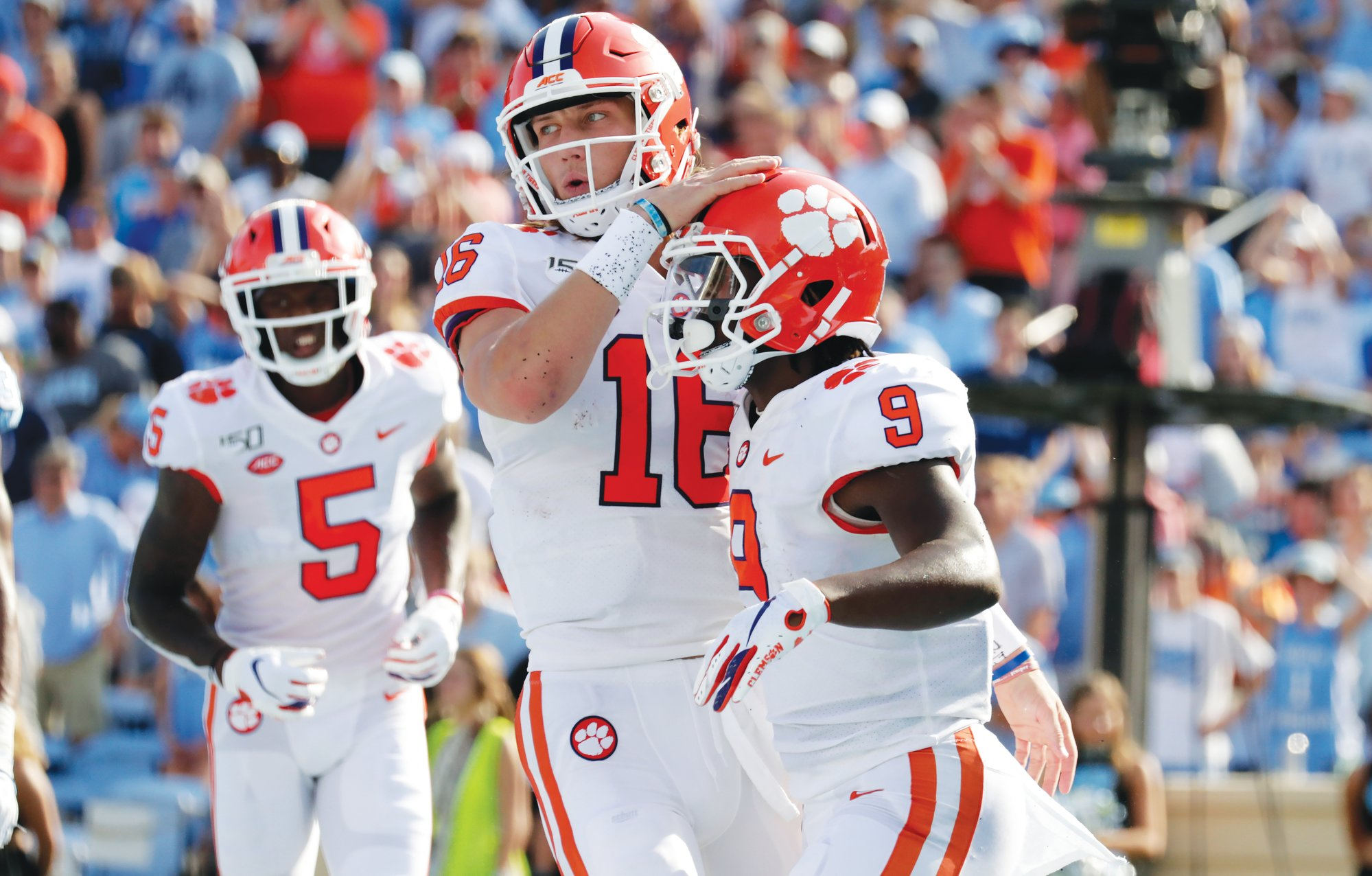 Clemson running back Travis Etienne (9) celebrates his touchdown with quarterback Trevor Lawrence (16) and wide receiver Tee Higgins (5) during the Tigers' 21-20 win over North Carolina in Chapel Hill, N.C., on Saturday.