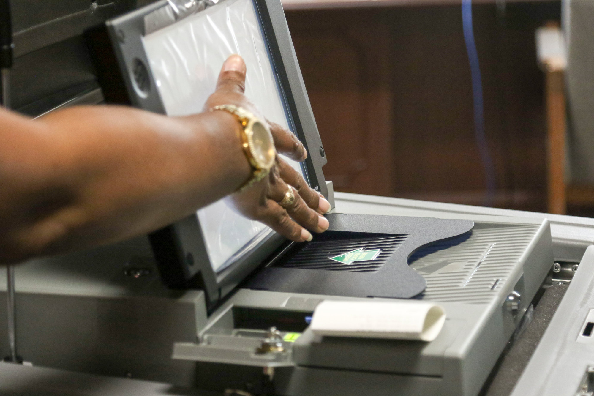 Ballot receipts are inserted into the top slot with the green arrow, and paper Scantron ballots are inserted into the larger slot below on the scanner machine.
