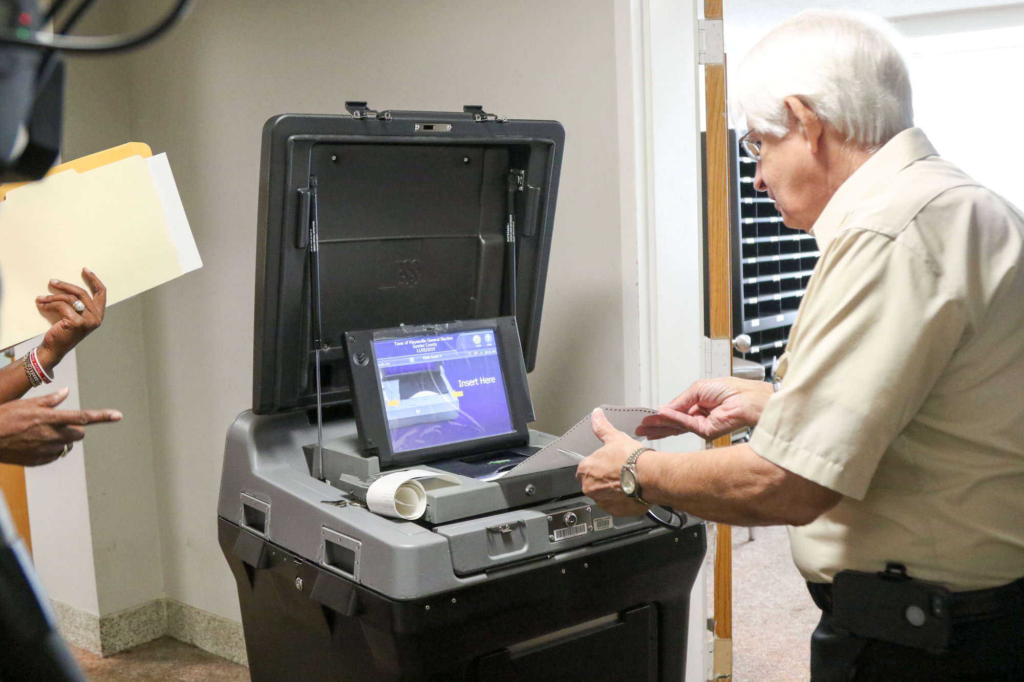 A member of the Sumter County Election Commission inserts his demo paper ballot into the scanner.