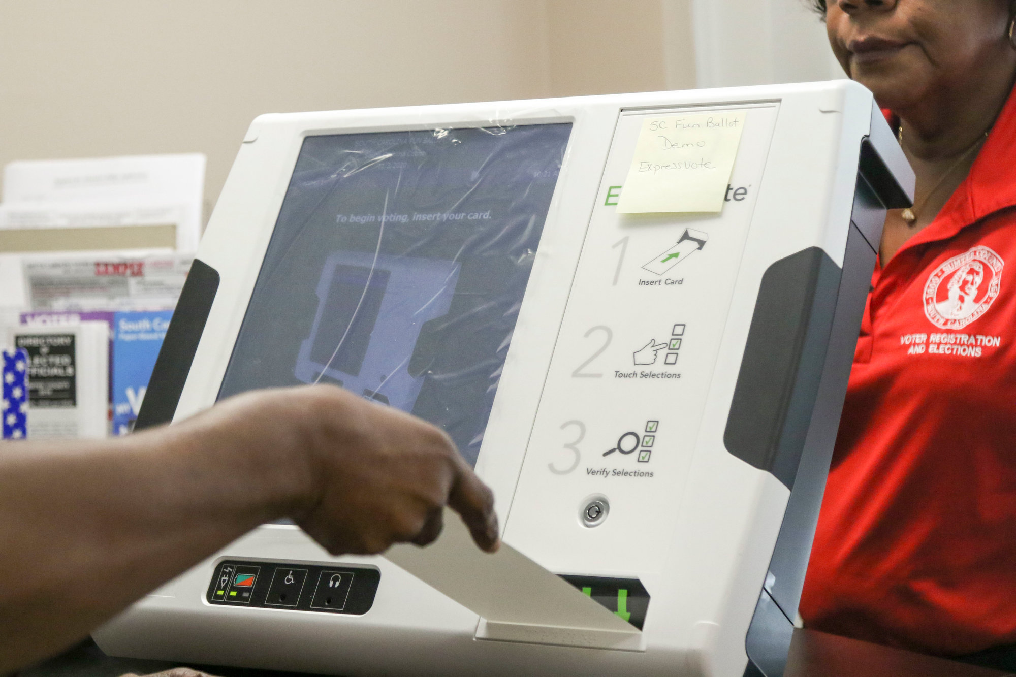 A blank ballot card is inserted. Once a voter makes selections on the touchscreen, the card is printed with those choices. Then, the card is inserted into a second machine to record the votes electronically and securely retain the paper copy for verification.