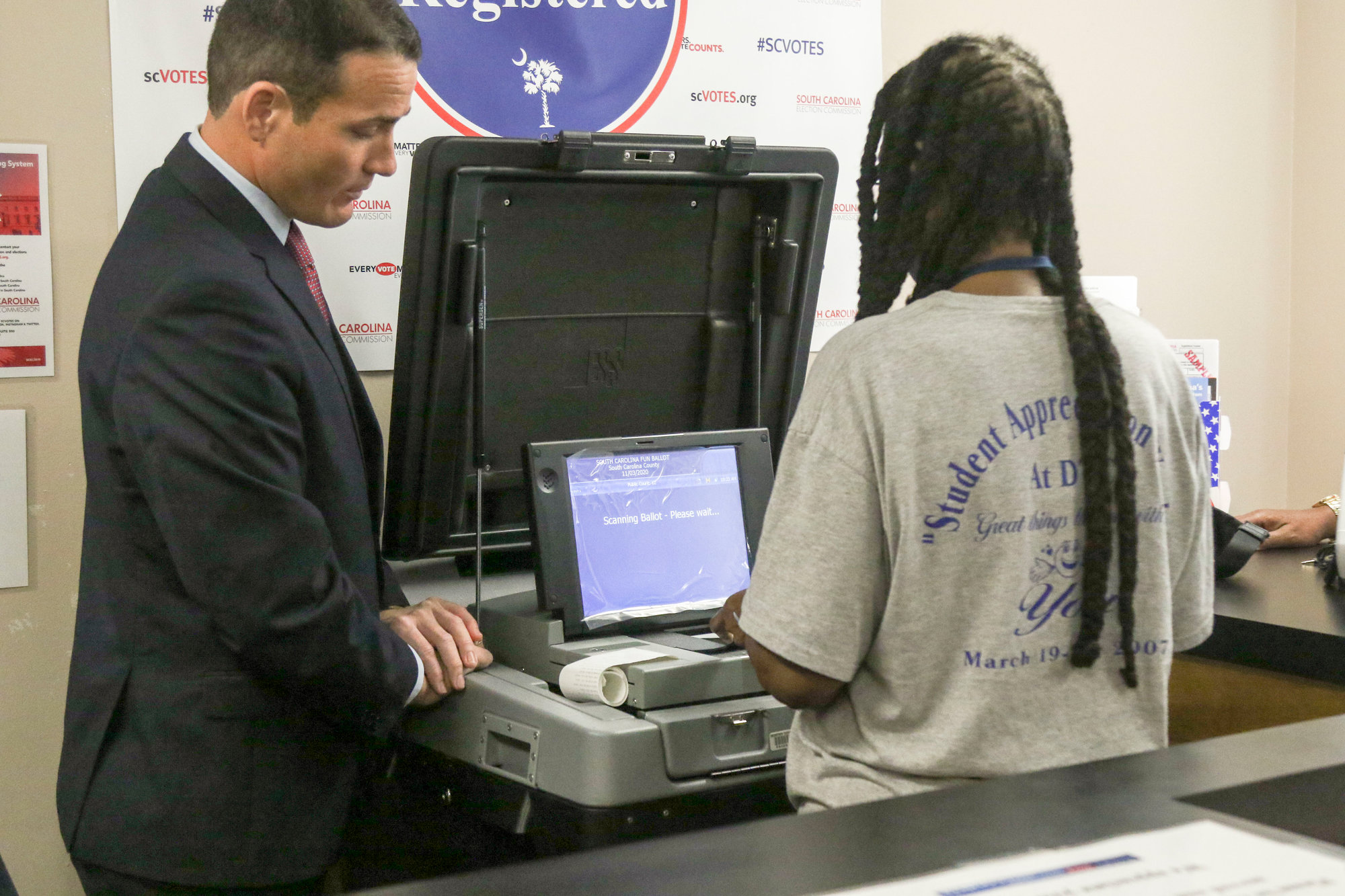 Trevor Ivey, a Sumter County election commissioner, and Mayesville Mayor Jereleen Hollimon-Miller demonstrate the scanner machine.