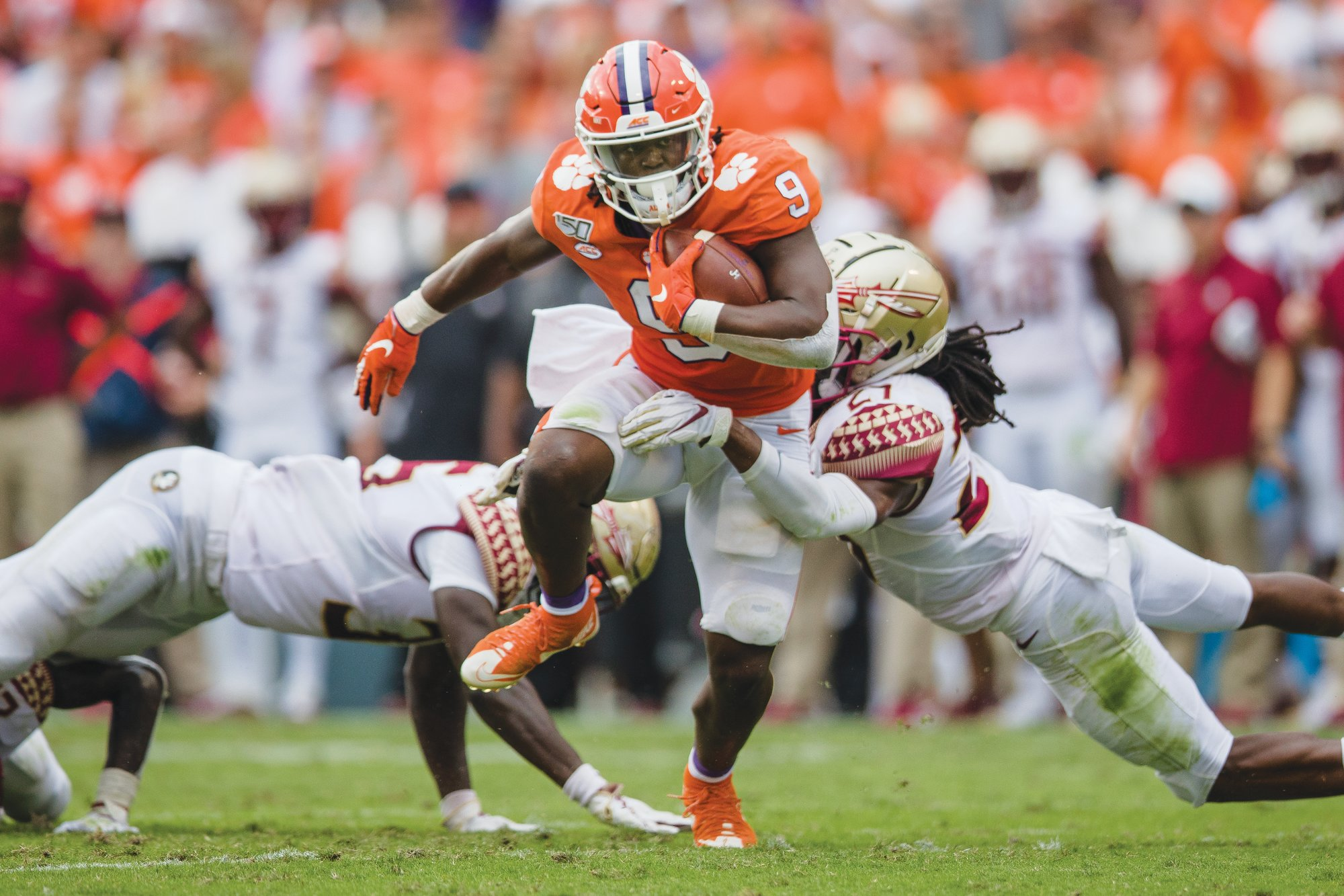Clemson's Travis Etienne (9) splits a pair of Florida State defenders during the Tigers' 45-14 victory on Saturday.