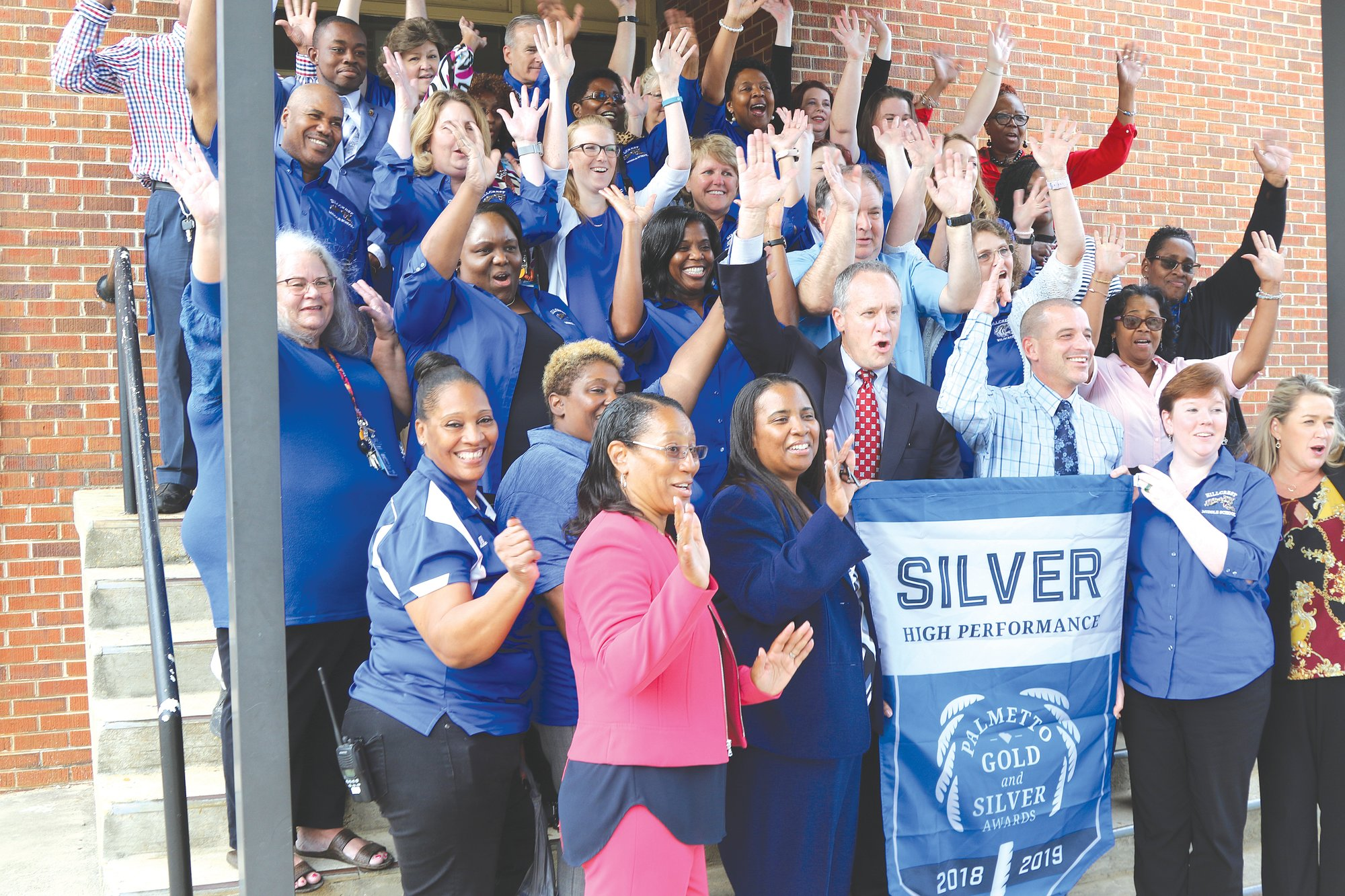 Sumter School District administrators and Hillcrest Middle School faculty and administration cheer themselves on Wednesday afternoon after receiving the school's Palmetto Silver Award banner for achievement from the state Department of Education.