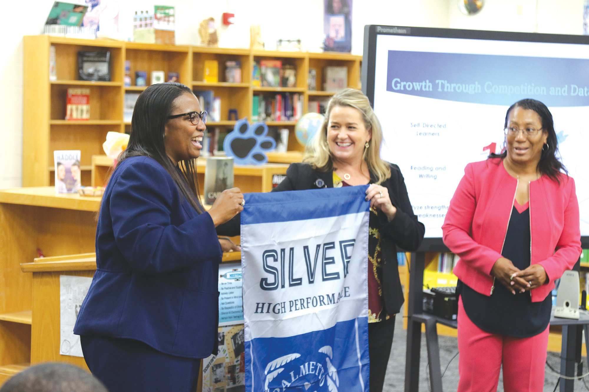 From left, Hillcrest Middle School Principal Tarsha Staggers and Sumter School District Chief of Schools Brenda Hafner share a light moment Wednesday during the banner presentation as Superintendent Penelope Martin-Knox looks on in the school's media center.