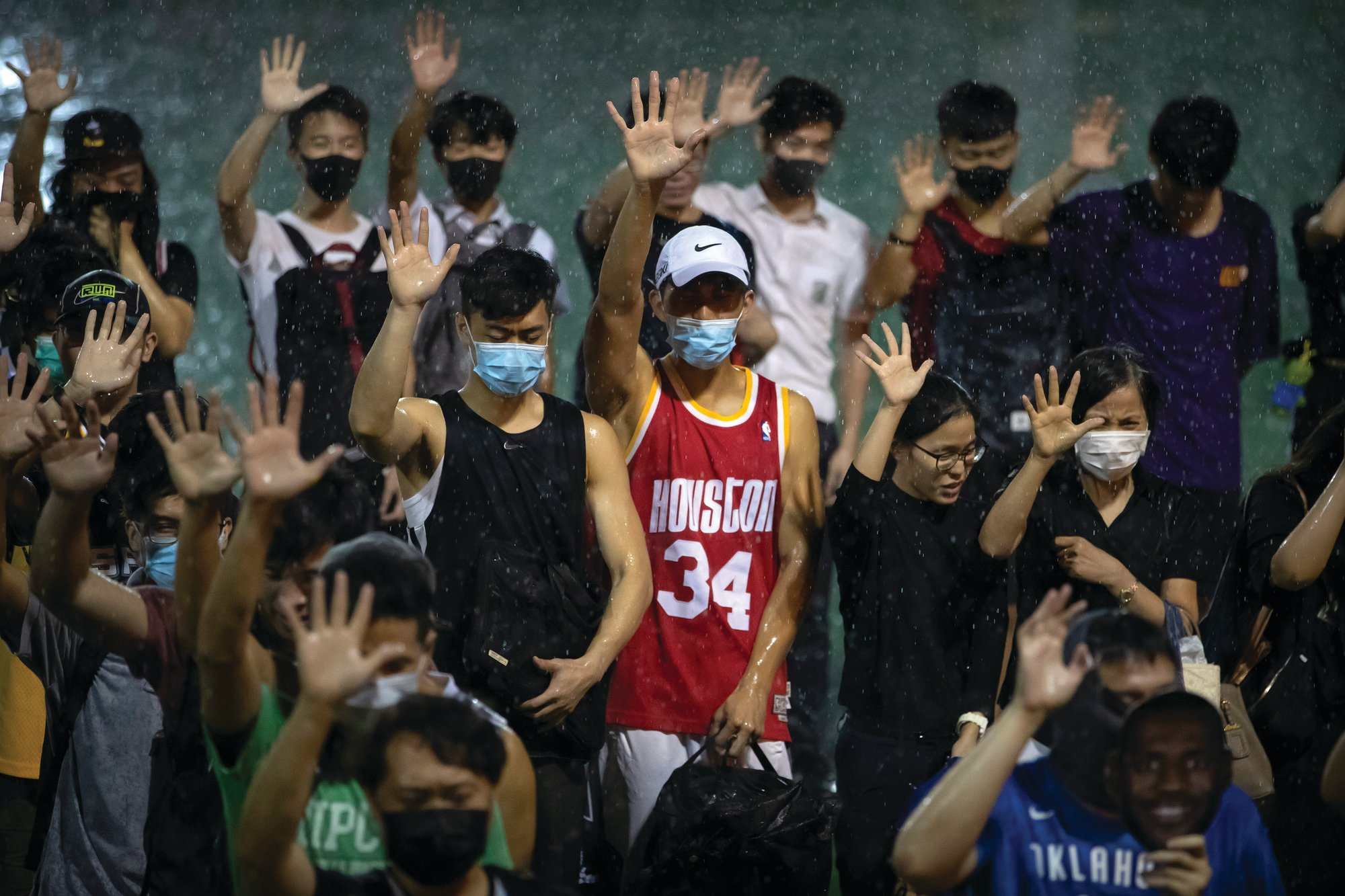 A demonstrator wearing a Houston Rockets jersey holds up his hand with fellow demonstrators during a rally at the Southorn Playground in Hong Kong on Tuesday. Protesters have thrown basketballs at a photo of LeBron James and chanted their anger about comments the Los Angeles Lakers star made about free speech.