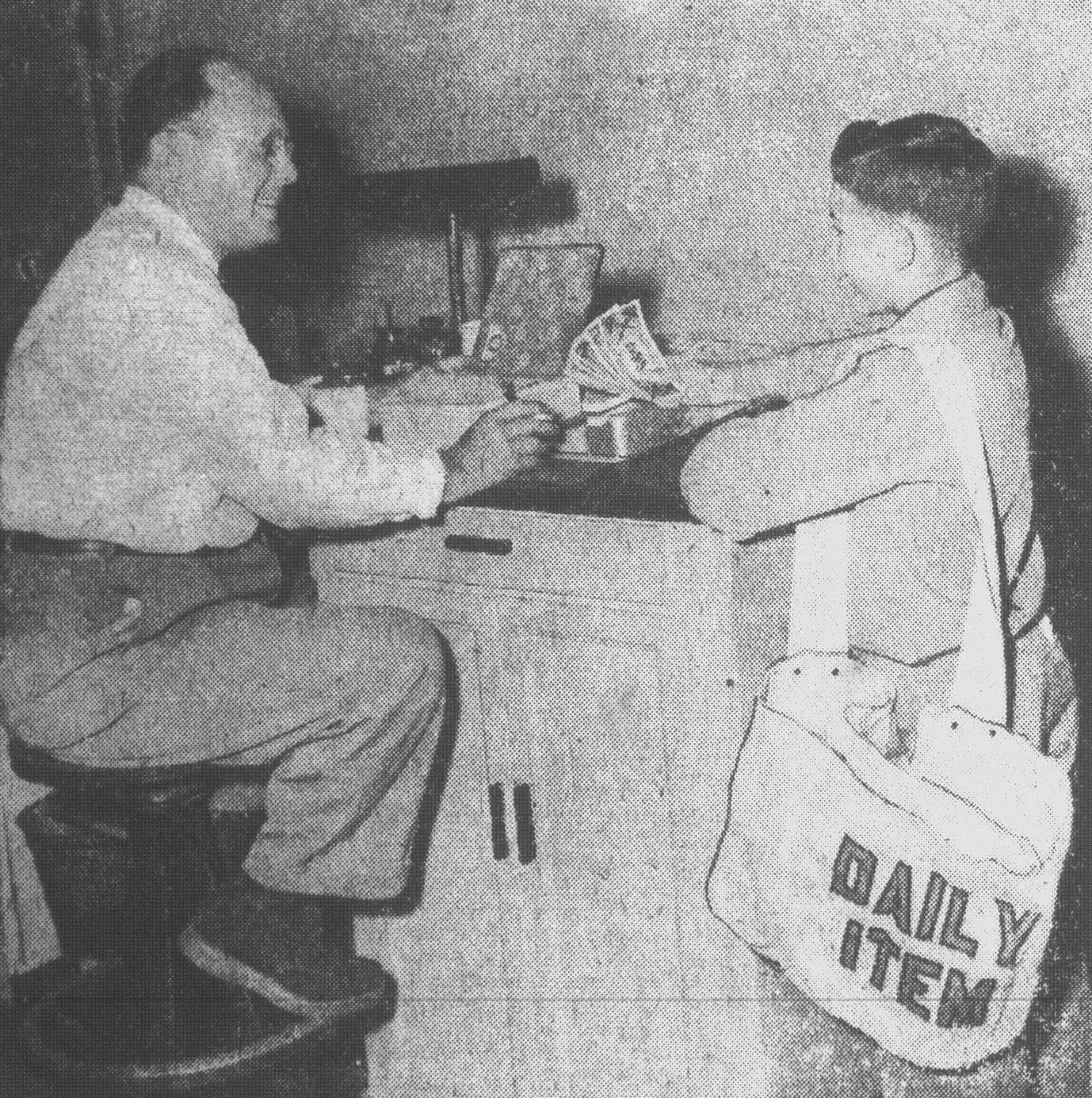 R. Mood Dollard and Jimmy Bateman are seen as they go through a regular weekly procedure at the Daily item office as National Newspaper Week gets underway in 1952. Mr. Dollard, circulation manager for the paper beginning in 1922, checked Bateman's route collection money.