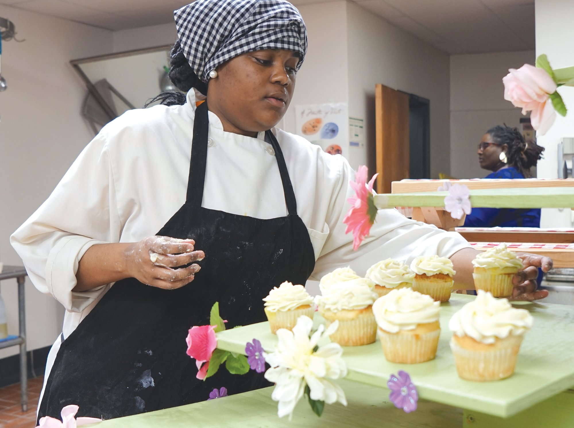Sumter High School senior Mikayah Anderson places her finished cupcakes on her spring display.