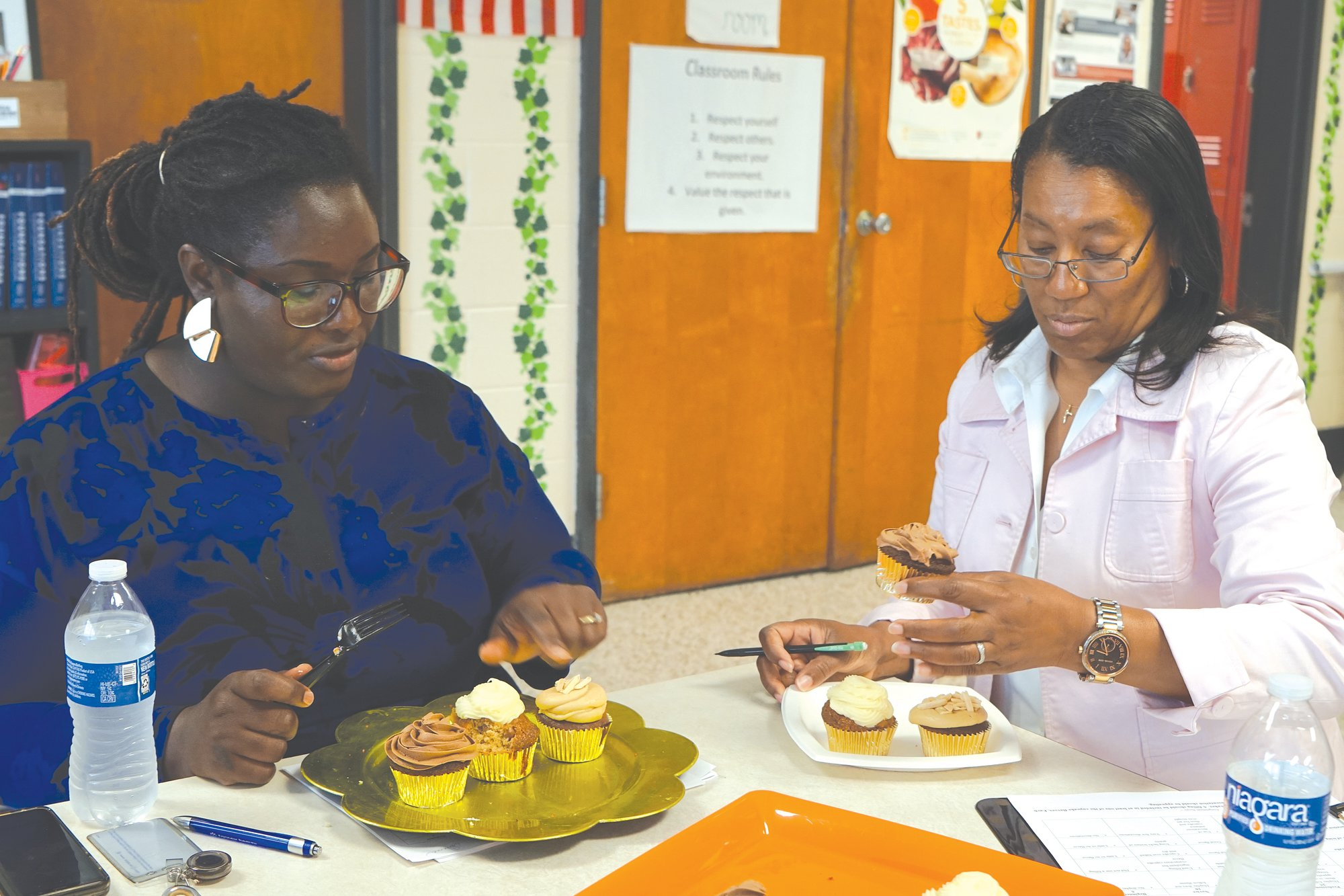 Judges Chef Kia Smith, left, and Sumter School District Superintendent Penelope Martin-Knox judge the appearance of the autumn cupcakes before taking a bite.