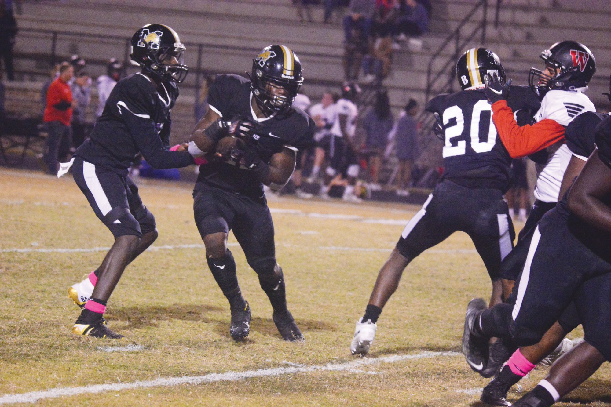 Manning quarterback Justin Daniels, left, hands the ball off to Aaron Smith during their 47-22 win over Waccamaw on Friday. Smith ran for four touchdowns on his way to Offensive Player of the Week honors.