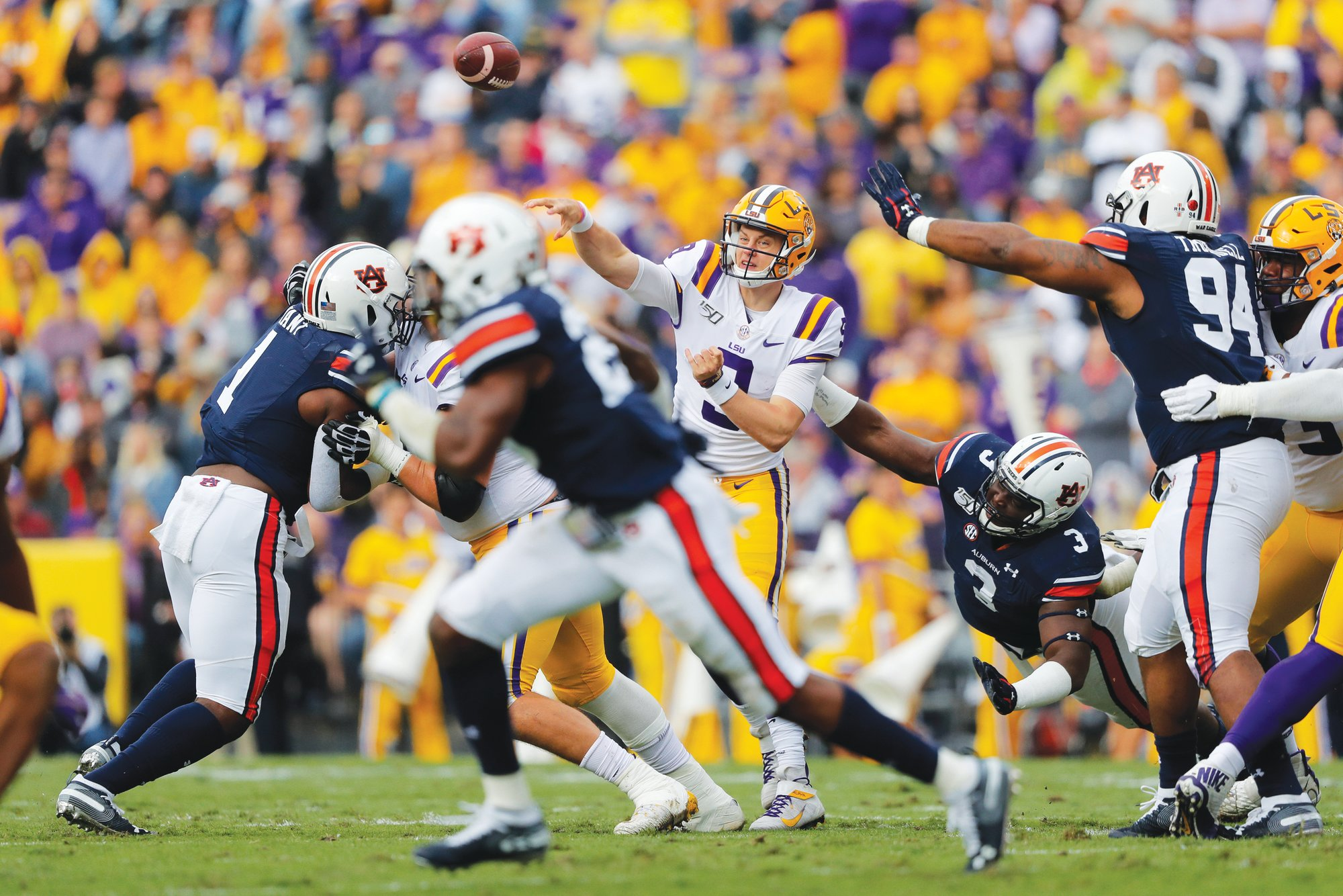 LSU quarterback Joe Burrow (9) passes under pressure from Auburn  defensive end Marlon Davidson (3) during the now top-ranked Tigers'  23-20 victory in Baton Rouge, La. on Saturday.