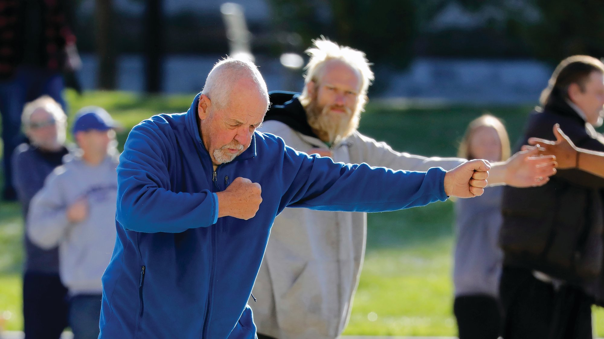 Bernie Hart, foreground, teaches tai chi in front of the Salt Lake Police headquarters, in Salt Lake City.