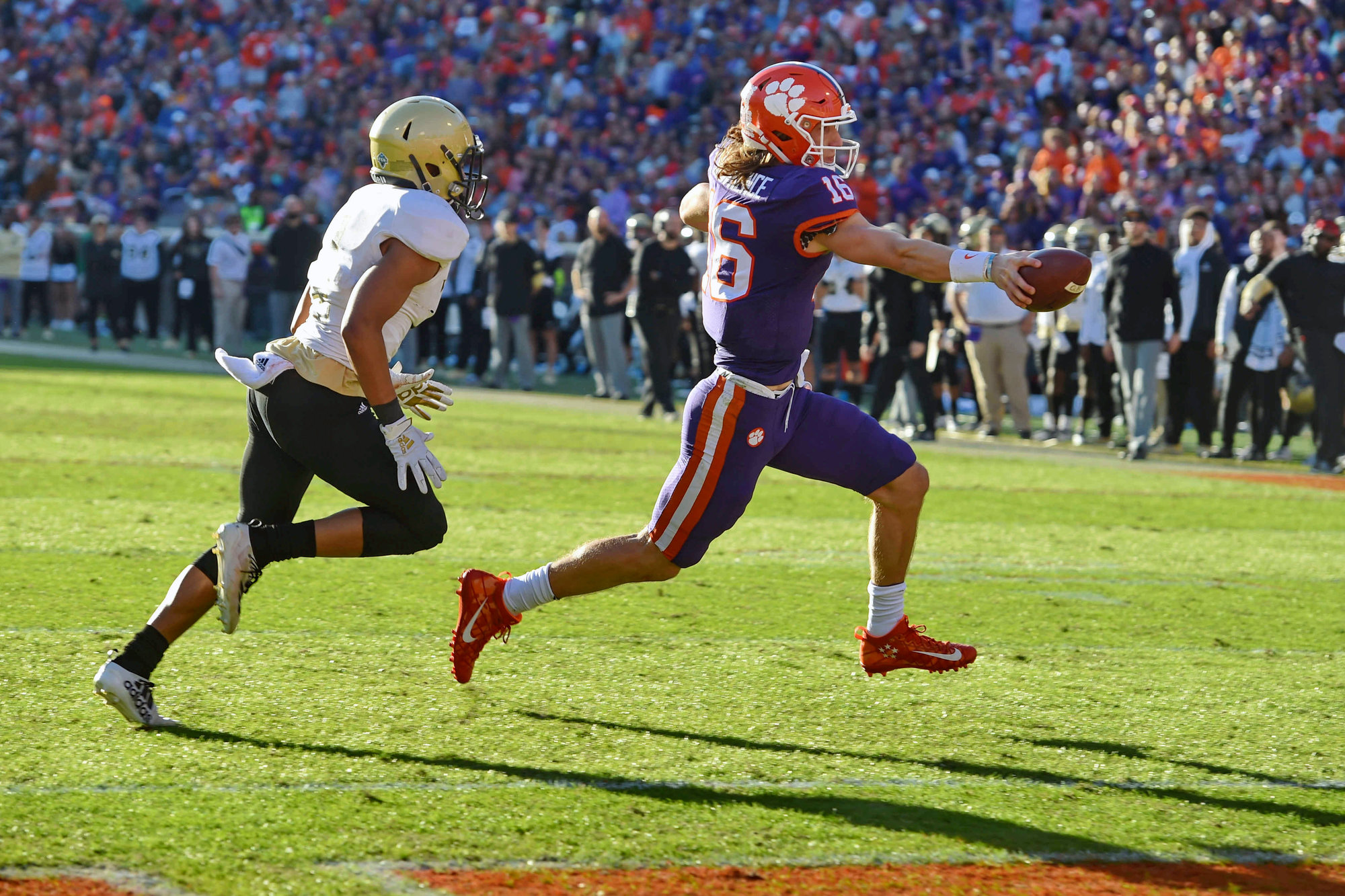 Clemson's Trevor Lawrence, front, scores a touchdown while defended by Wofford's Keyvaun Cobb during the first half of an NCAA college football game Saturday, Nov. 2, 2019,  in Clemson,  S.C.