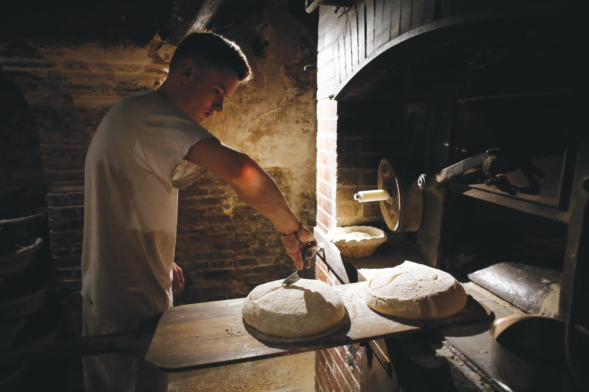 A worker prepares round loaves for baking in the bread oven of the Poil ne bakery in Paris.