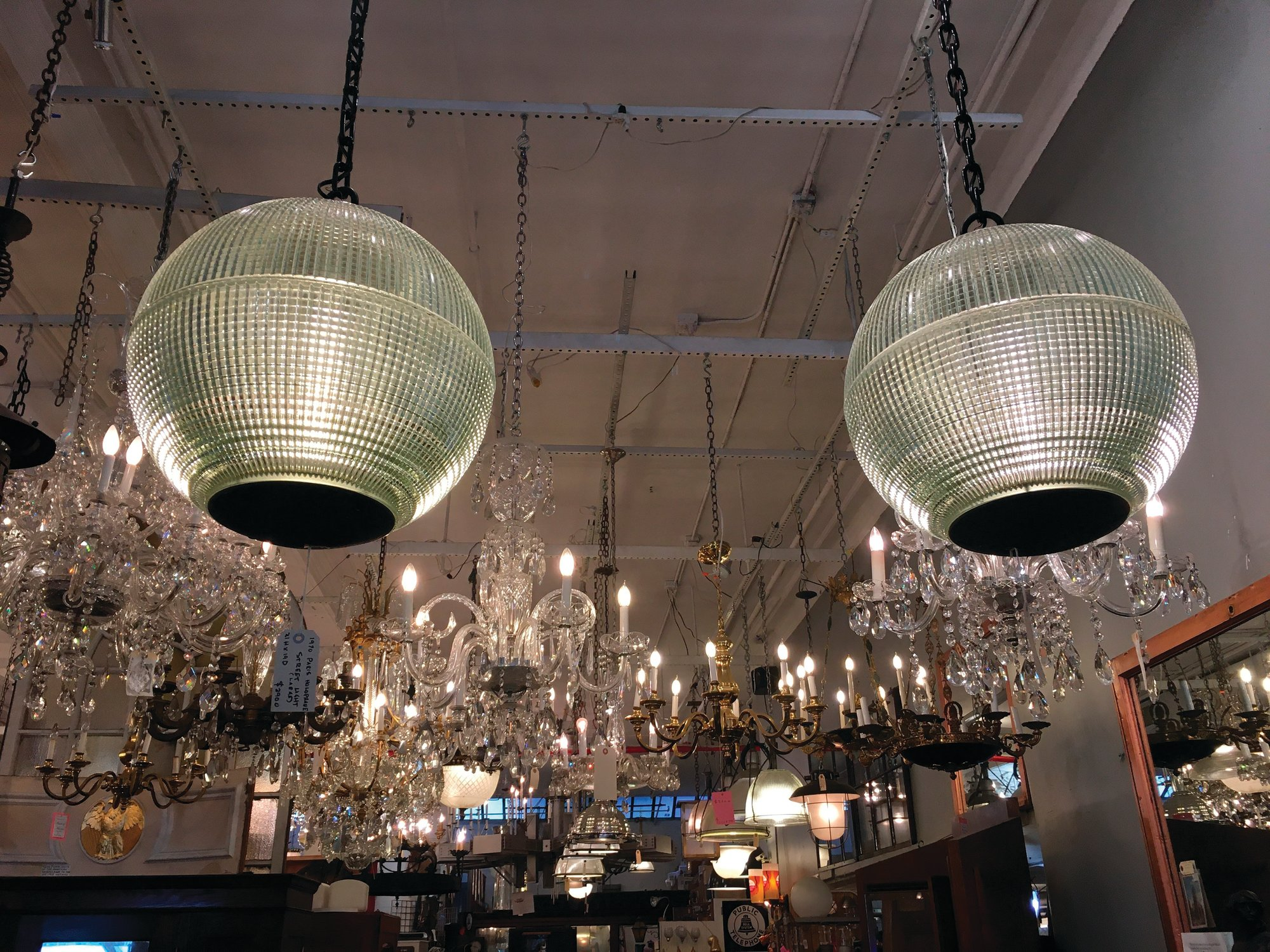 Seen are two light fixtures reconfigured as pendant lamps from Paris street lamps, available for sale at Olde Good Things salvage store in New York.
