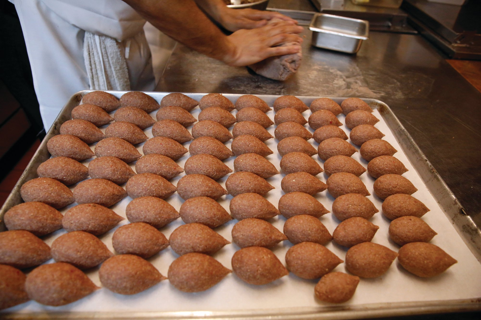 Chef Diaa Alhanoun rolls out ground meat while preparing kibbeh. Kibbeh meatballs are a made of ground beef, bulgur wheat and onions, seasoned with cinnamon and allspice, formed into a hollow shell for stuffing, then deep fried or baked.