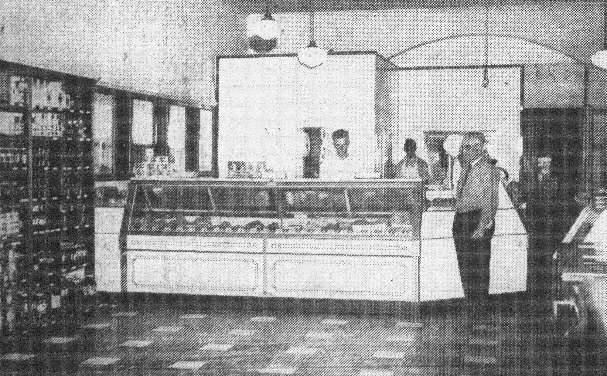 "The meat market at H.J. Commins' remodeled store featured quality meats and built up a large business after it opened. Standing in front of the display case is H.J. Commins, and behind the case is Norwood ""Buck"" Epperson, meat market manager."